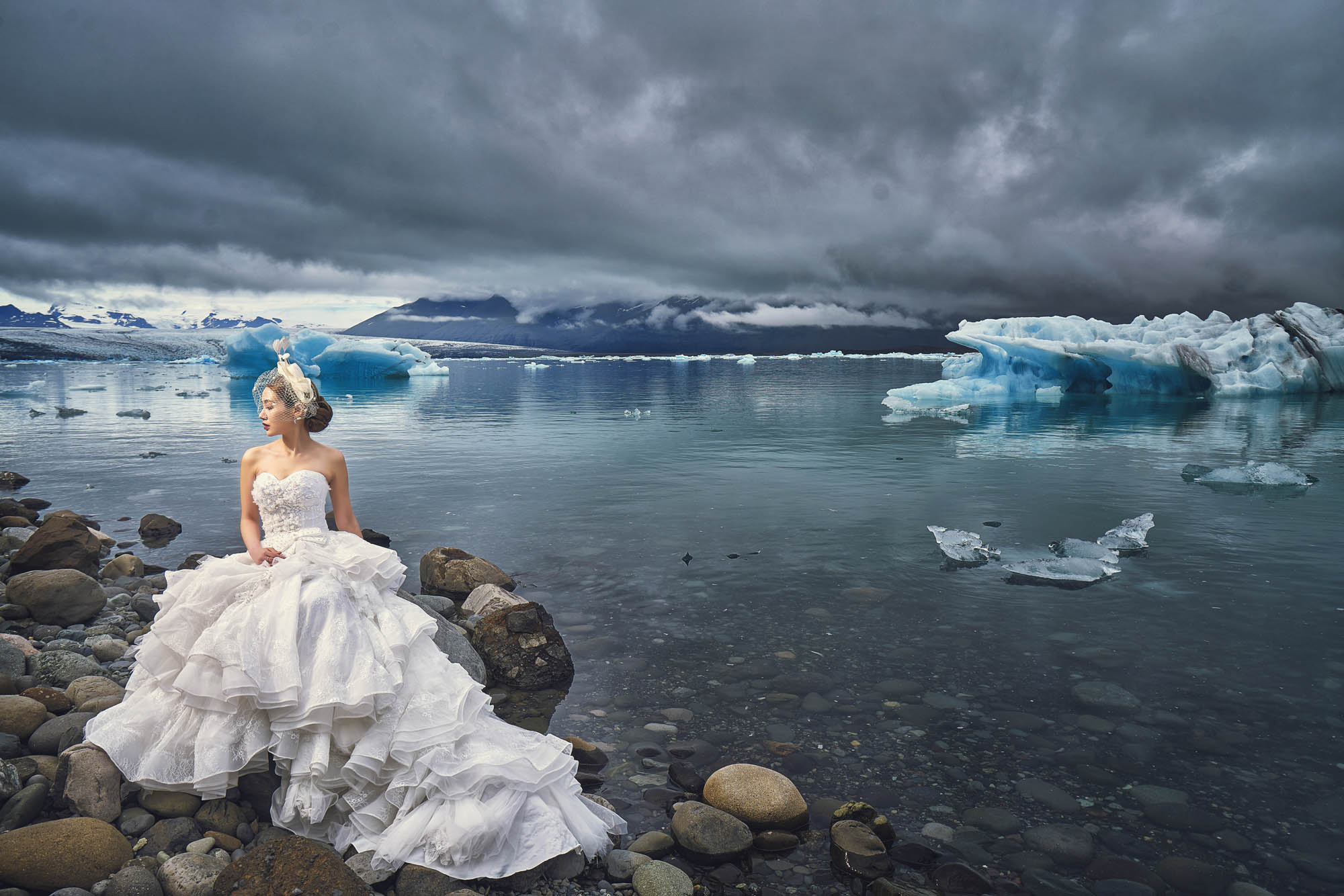 Bride on icy beach with ruffled gown and birdcage veil - photo by CM Leung - Hong Kong
