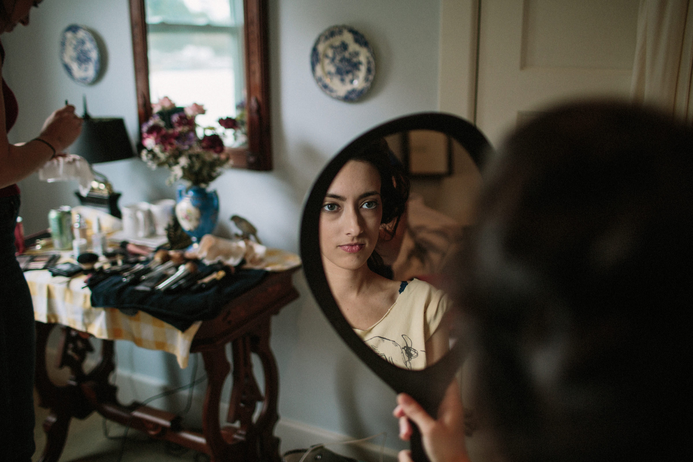 Bride getting ready reflected in hand mirror - photographed by Jonas Seaman