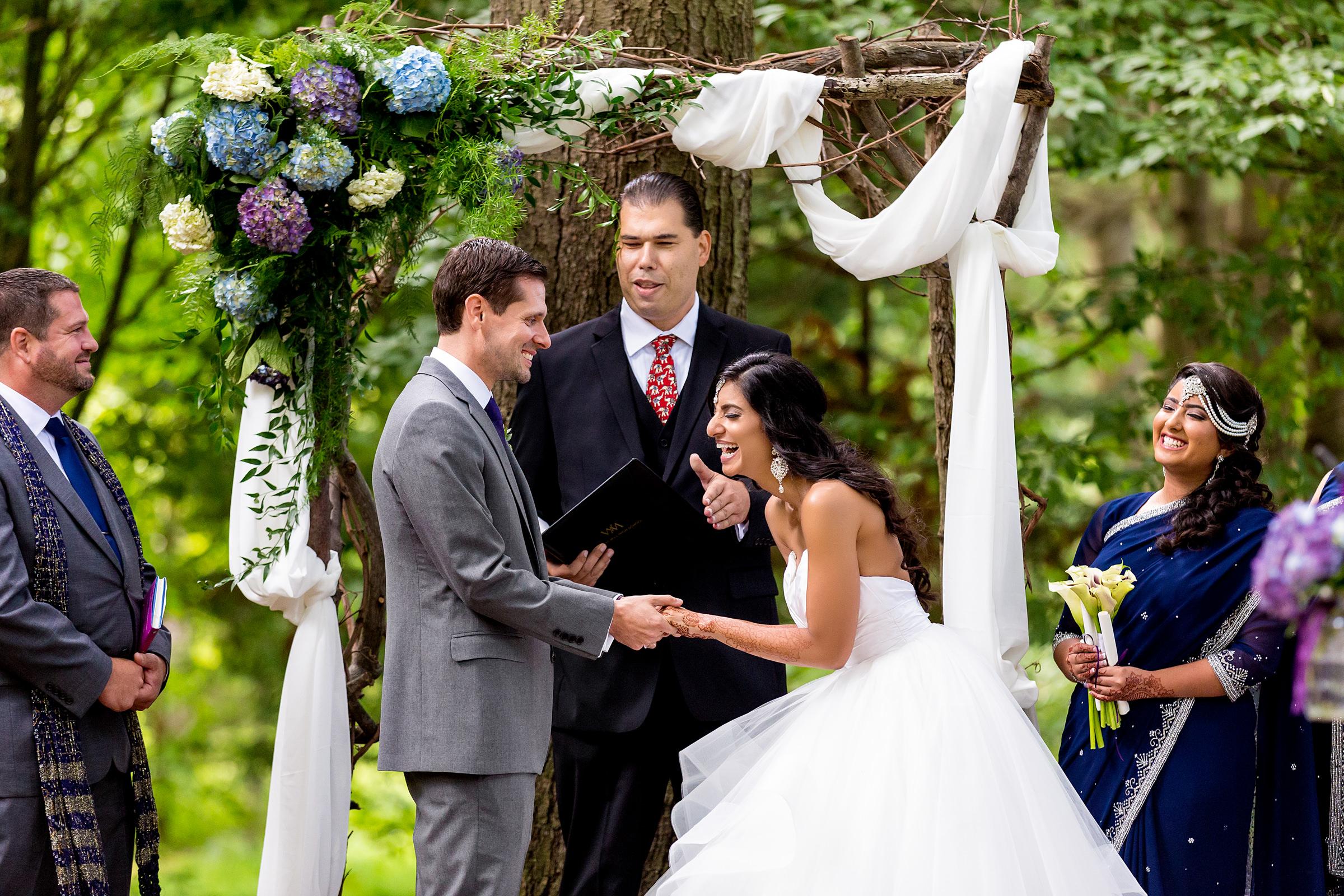 bride-laughs-during-ceremony-under-arbor-procopio-photography
