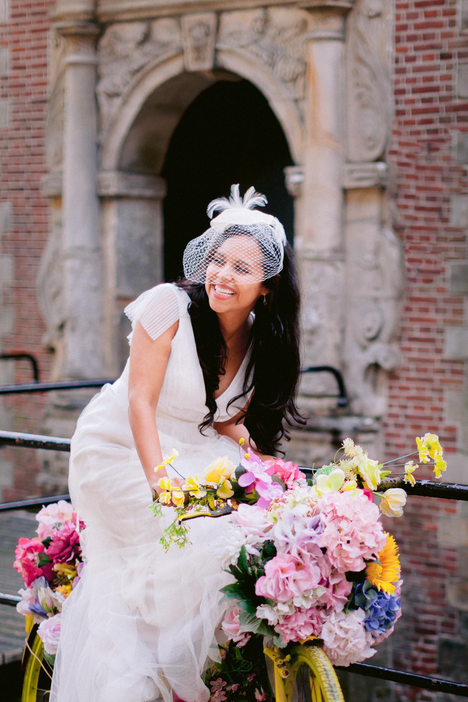 Bride on pink bicycle wearing birdcage veil - photo by Peter van der Lingen - Netherlands