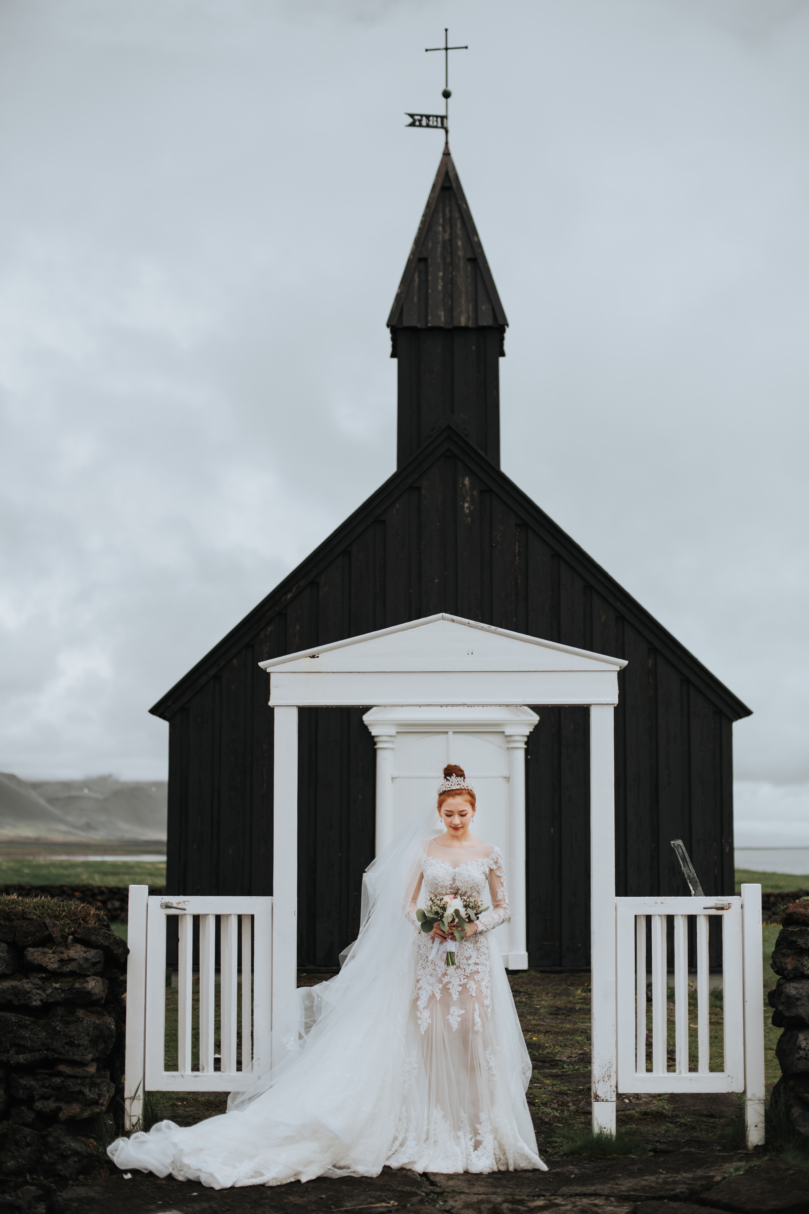 Bride in lace gown in front of small black and white church - photo by Mun Keat Studio