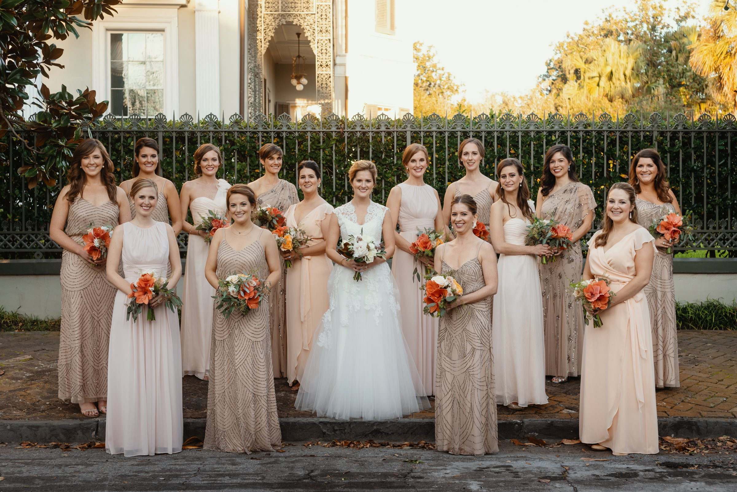 Bride posing with bridesmaids wearing soft apricot and beaded taupe gowns - photographed by Dark Roux - New Orleans