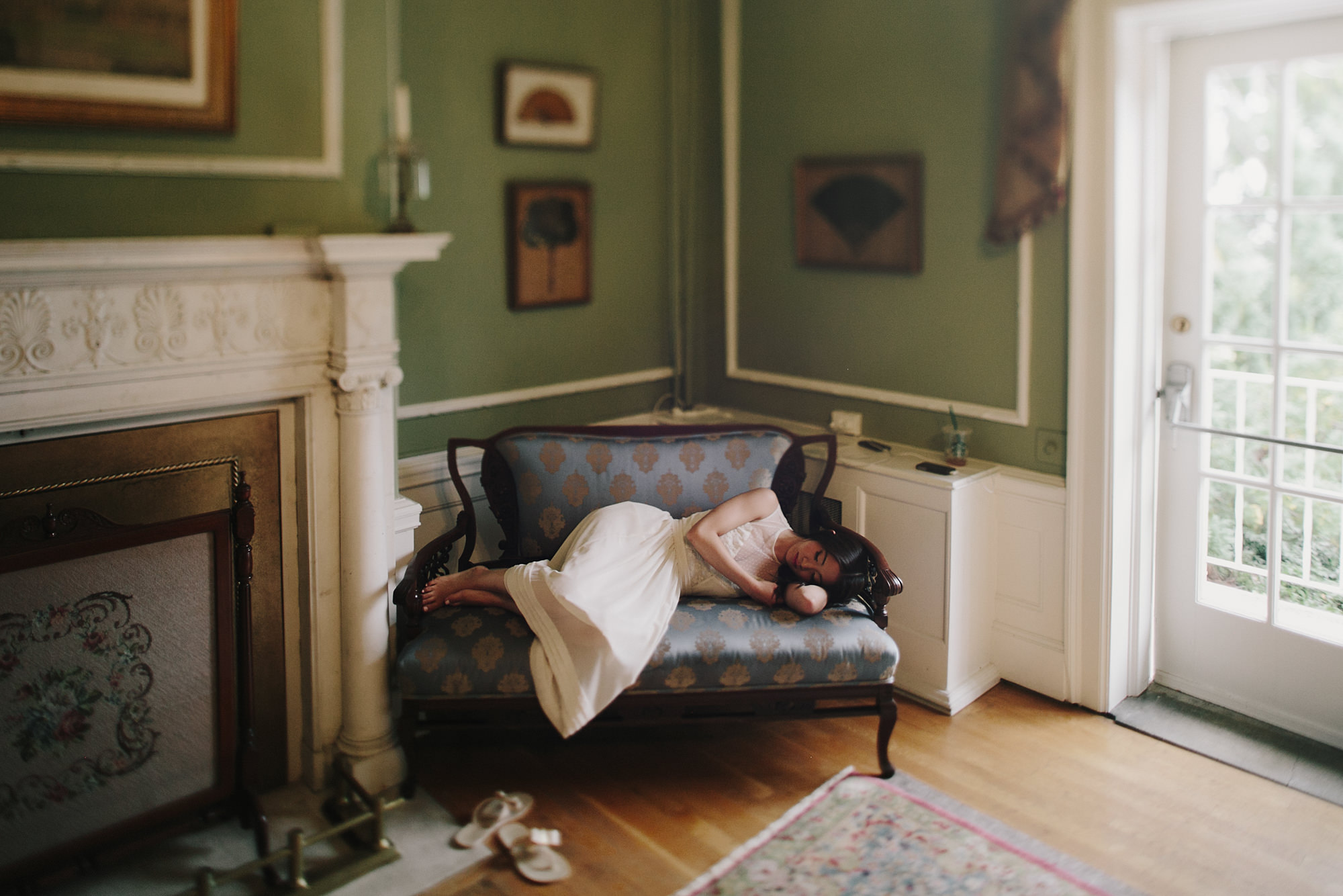 Bride rests before ceremony on silk loveseat - photo by James Moes - Missouri