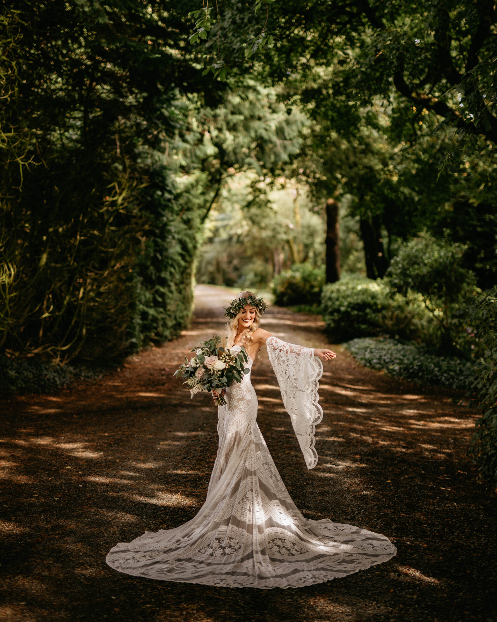 bride-with-floral-crown-and-large-bouquet-on-tree-lined-road-lima-conlon-photography
