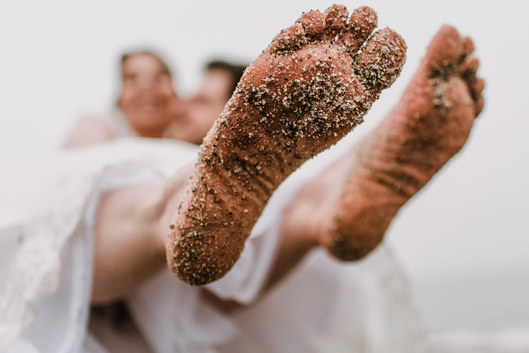 The bottom of brides feet being carried away by groom - photo by Rich Howman - UK