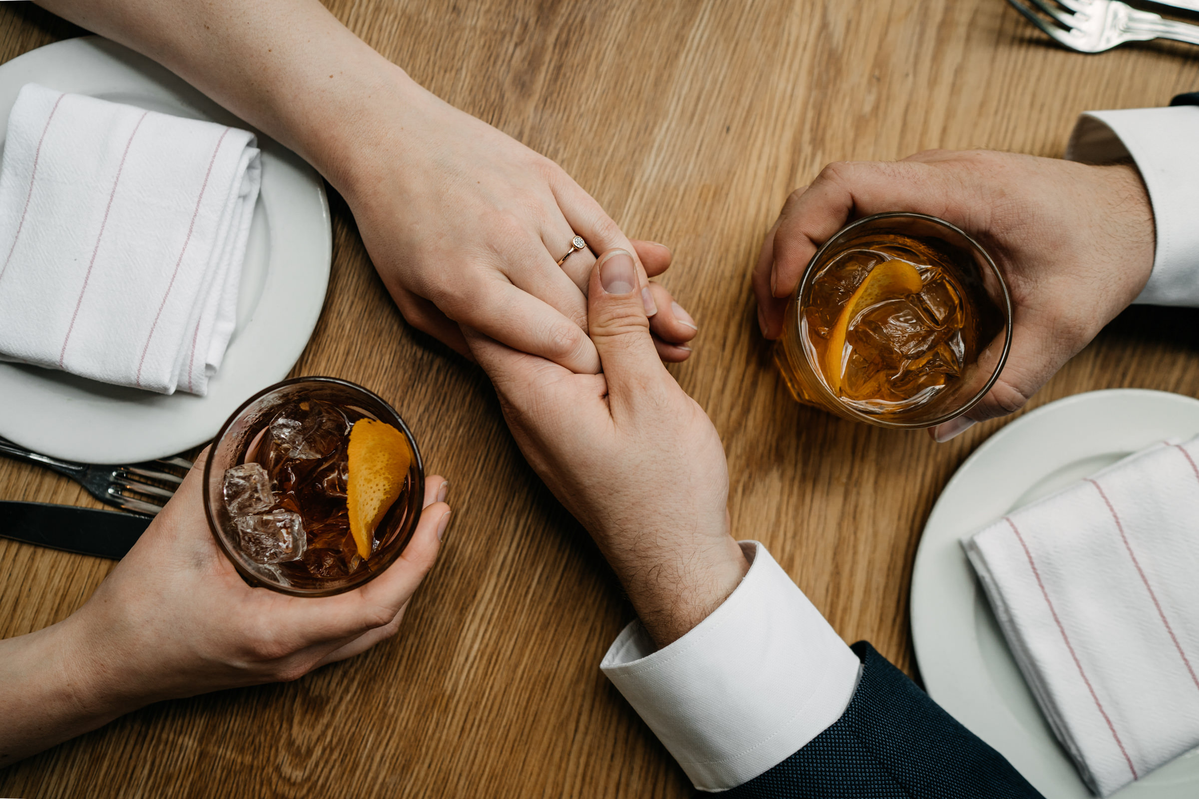 Bride and groom hold hands over glasses of whiskey - photo by Sasha Reiko - Seattle