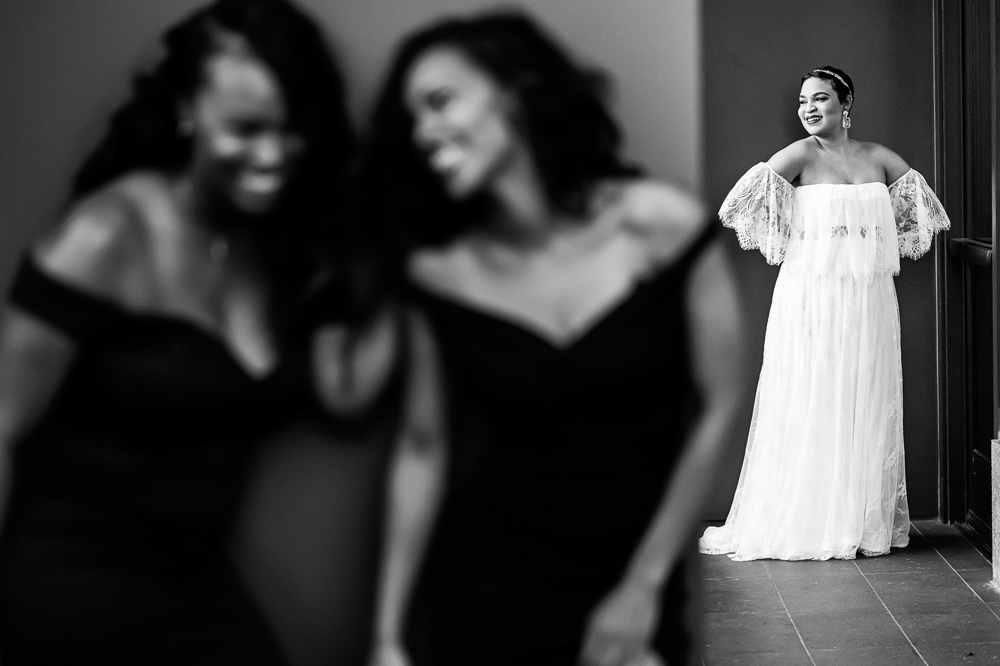 bridemaids-laugh-in-foreground-while-bride-in-lace-dress-has-her-portrait-taken-christopher-jason-studios