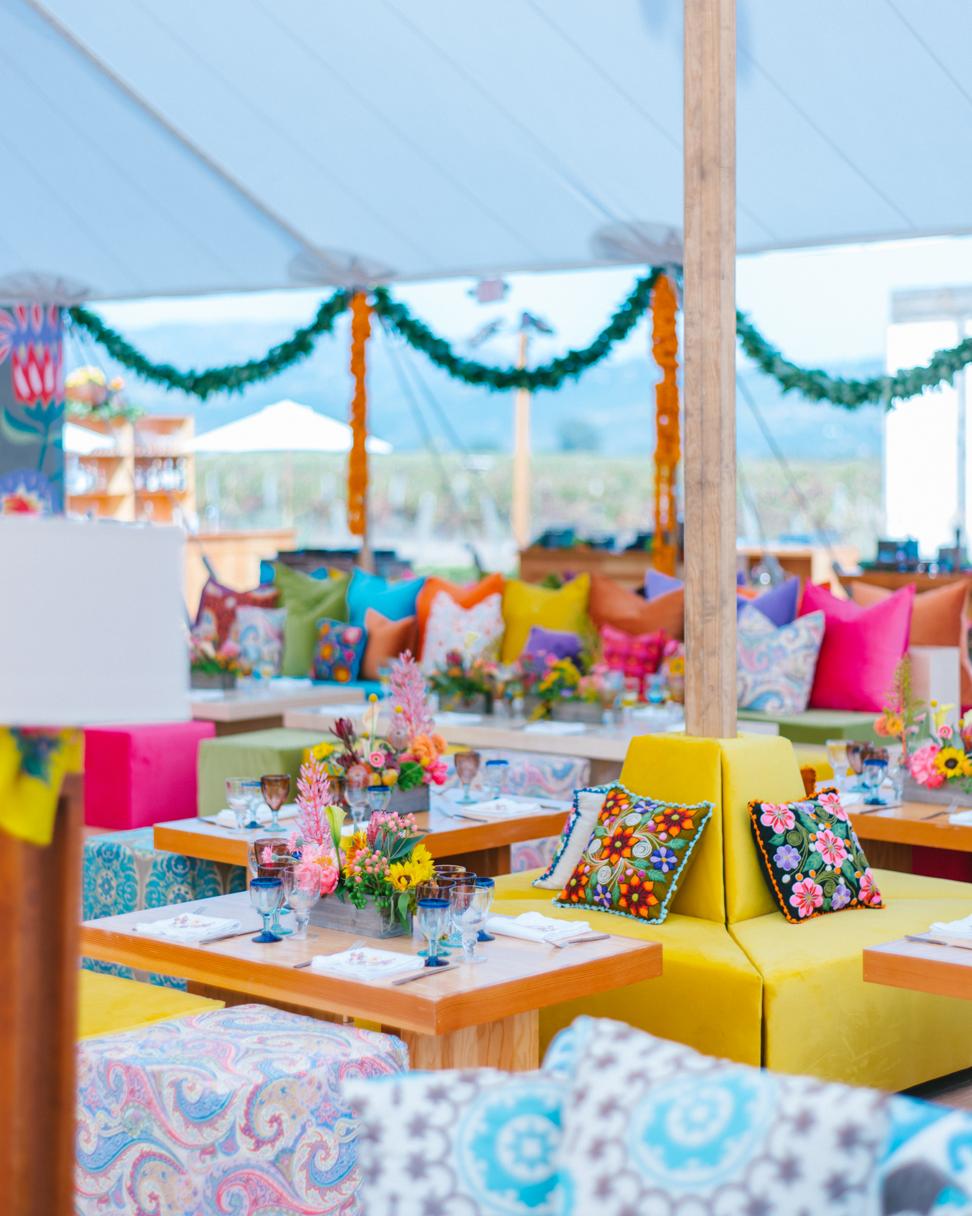 Bright, summery tent with floral pillows and pink Protea flowers