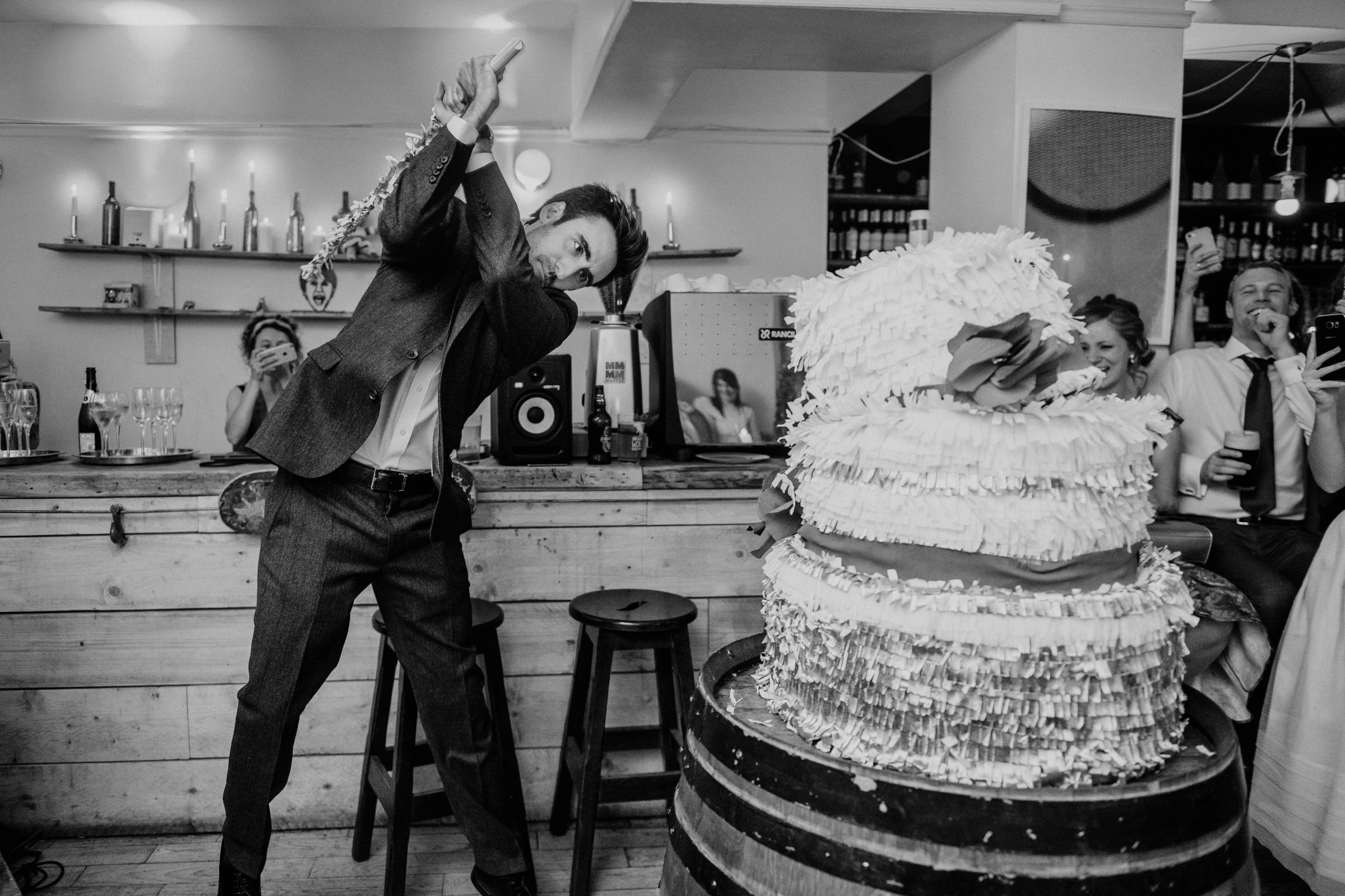 Groom attacks piñata wedding cake with a wooden sword - photo by John Gillooley - Ireland