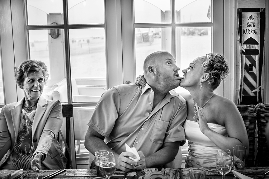 Bride biting her husband's lip - photo by Studio Damon Photography