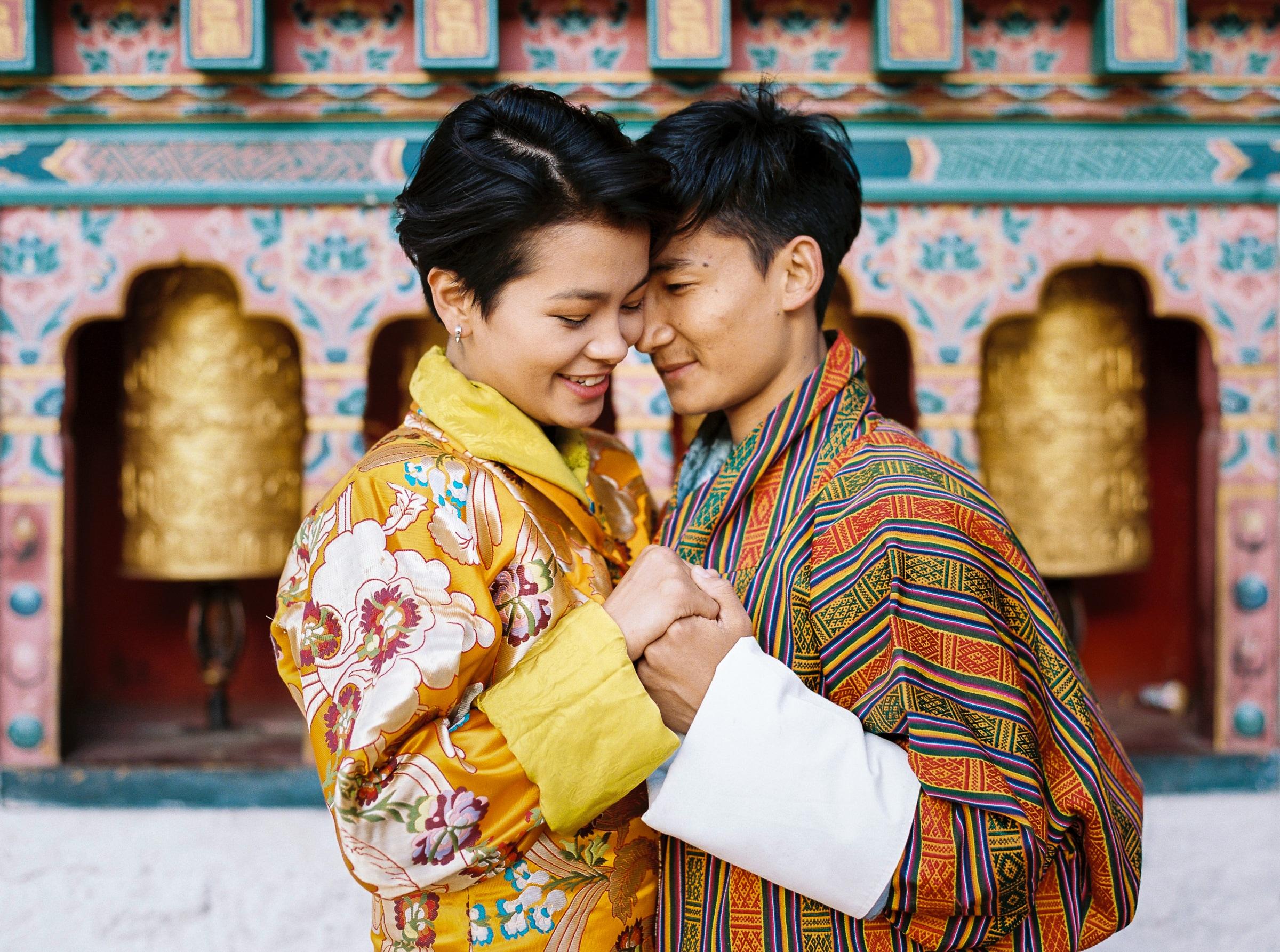 couple-against-temple-with-prayer-wheels-sylvain-bouzat-wedding-photographer