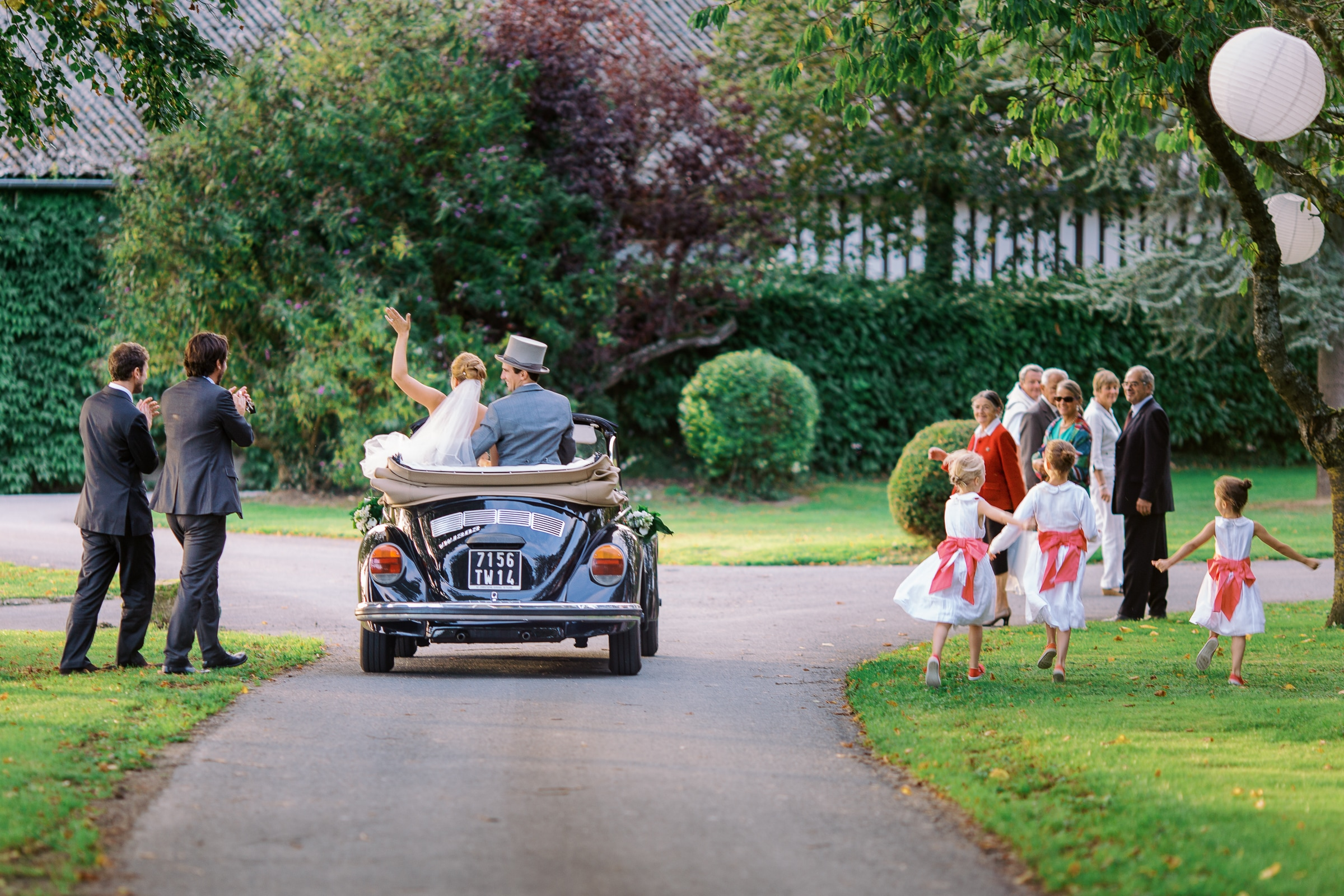 Bride and groom wave goodbye in blue VW bug convertible - photo by Sylvain Bouzat