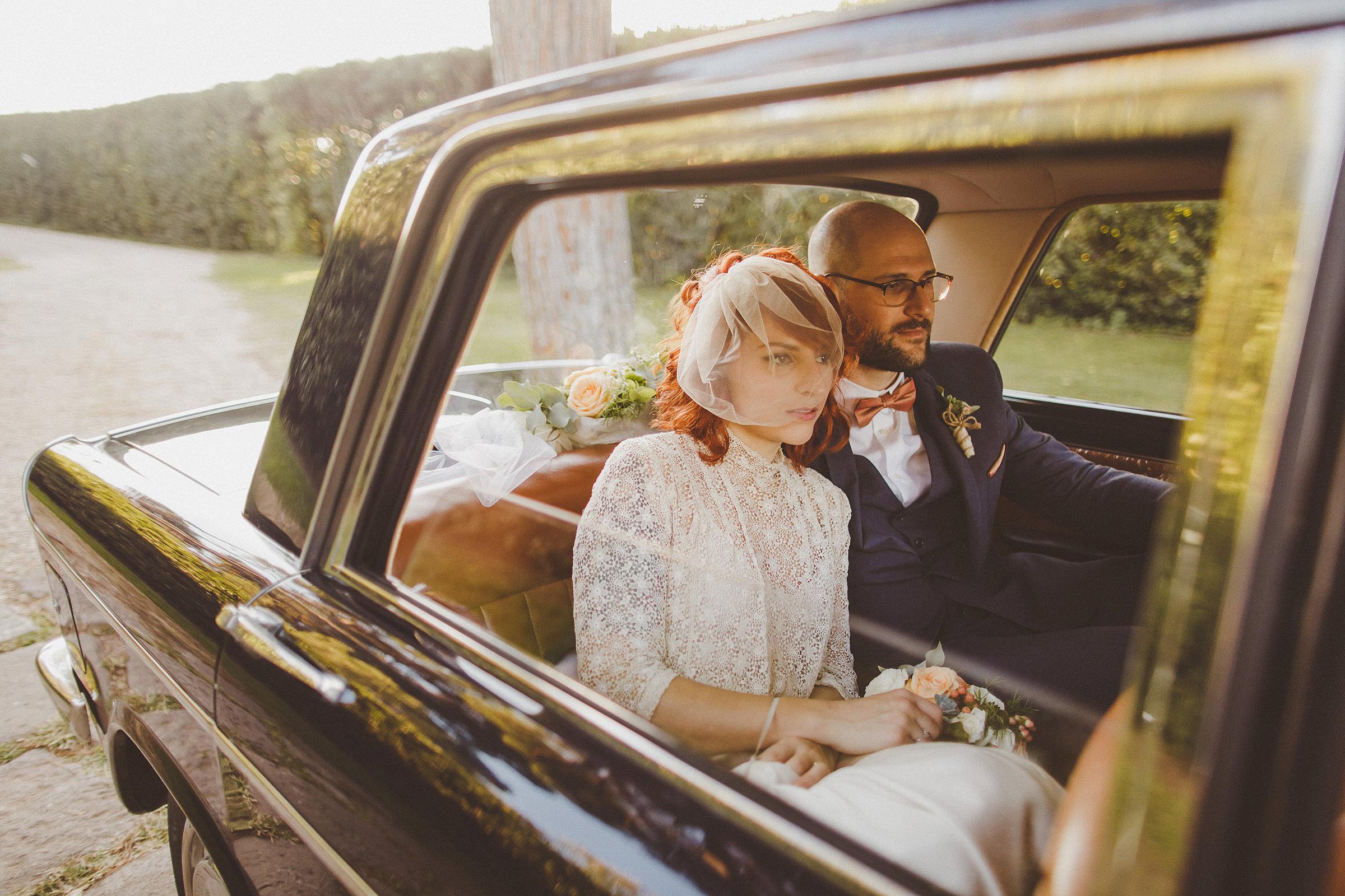 Bride wearing minimalist bird cage veil in back of vintage car - photo by Ed Peers - England