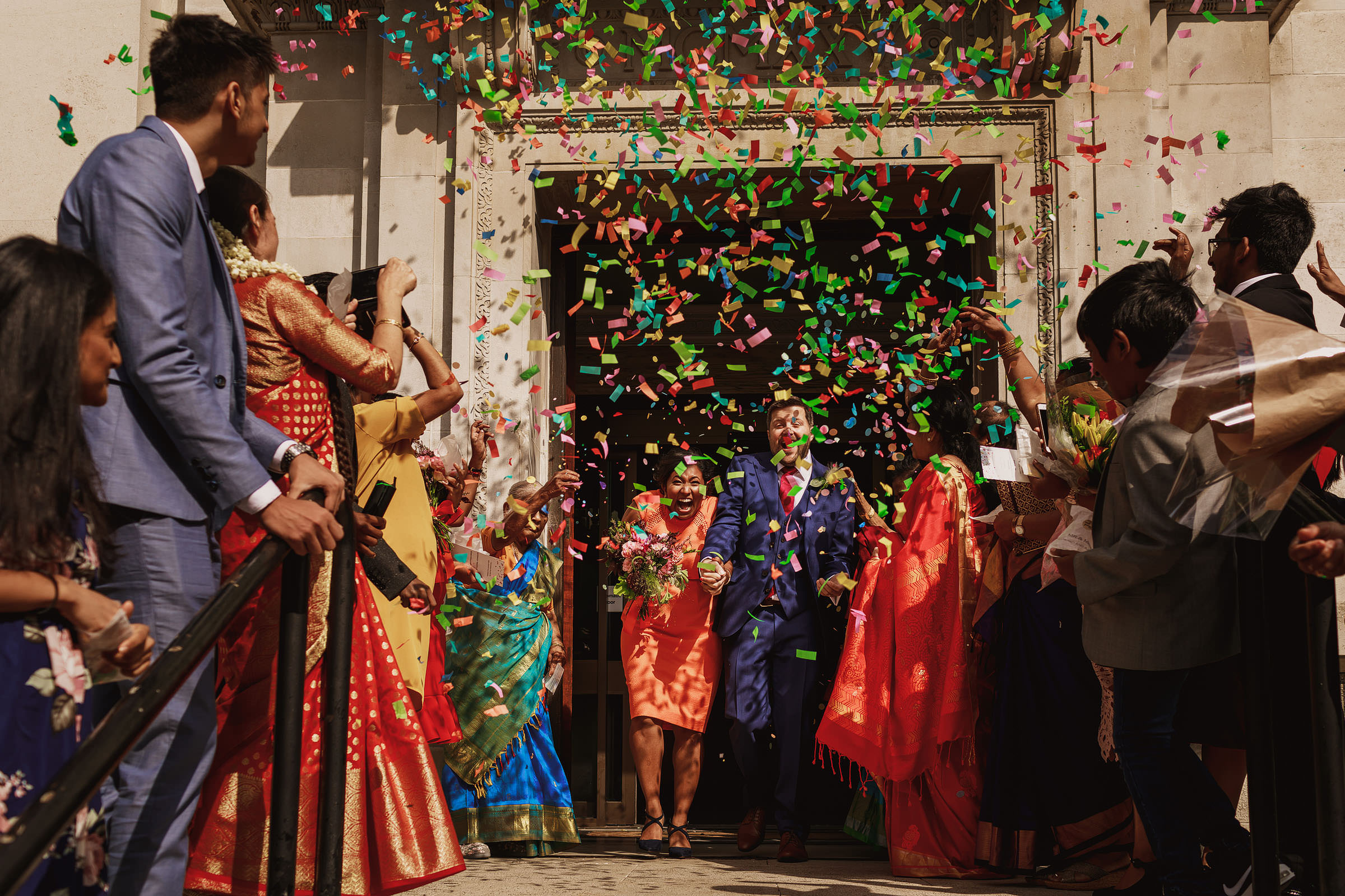 Couple exits under colorful confetti photographed by f5 Photography - London