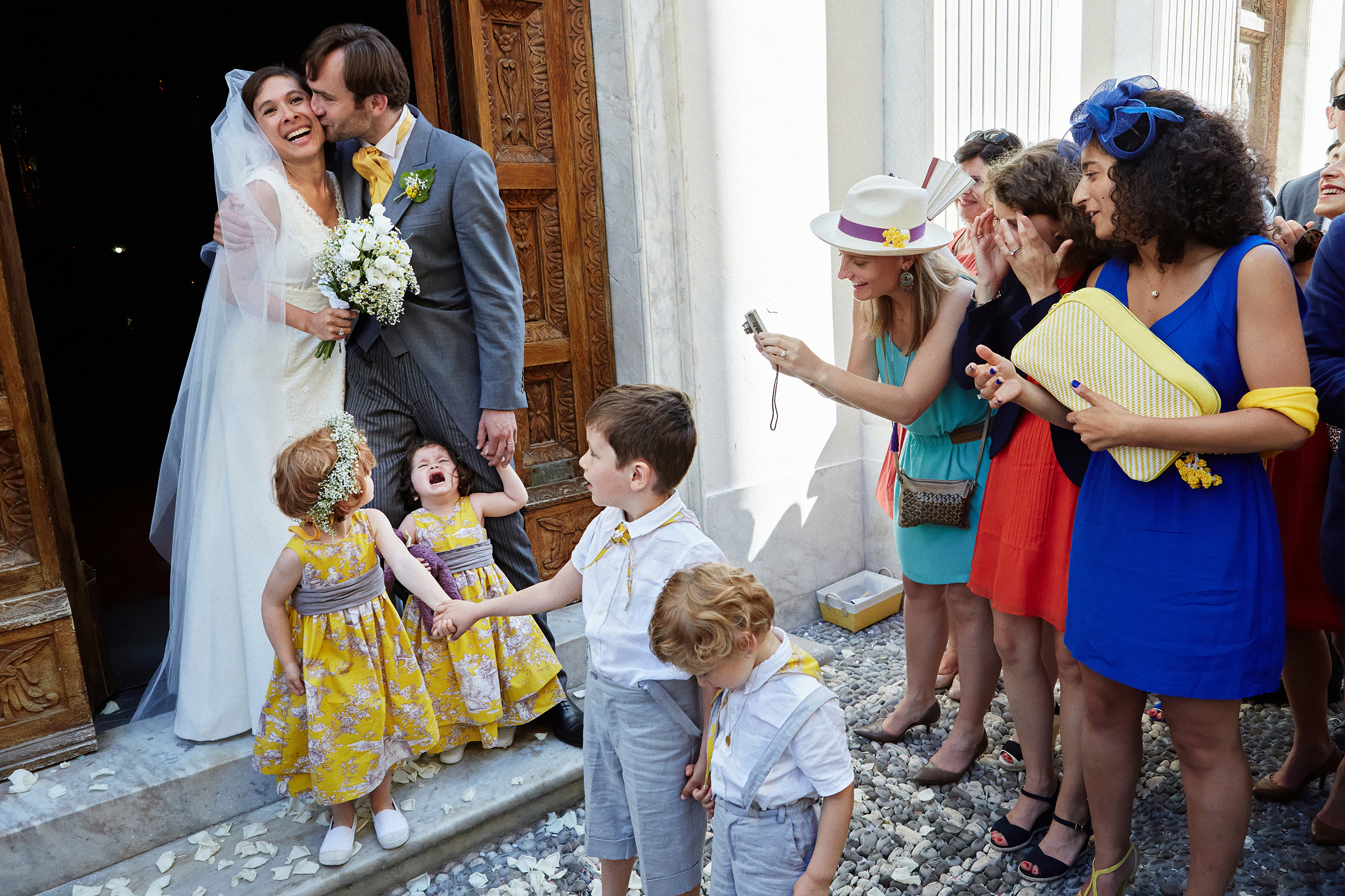 couple-kiss-amidst-small-children-and-guests-andrea-bagnasco-fotografie