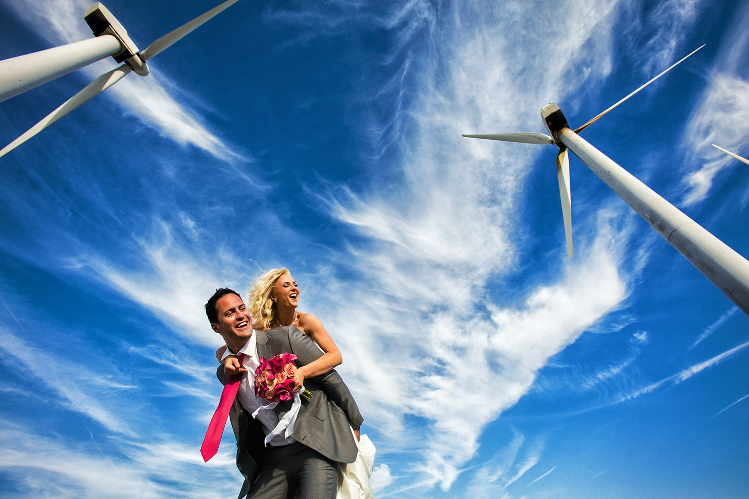 Upbeat couple playing in a wind farm field - photo by Callaway Gable