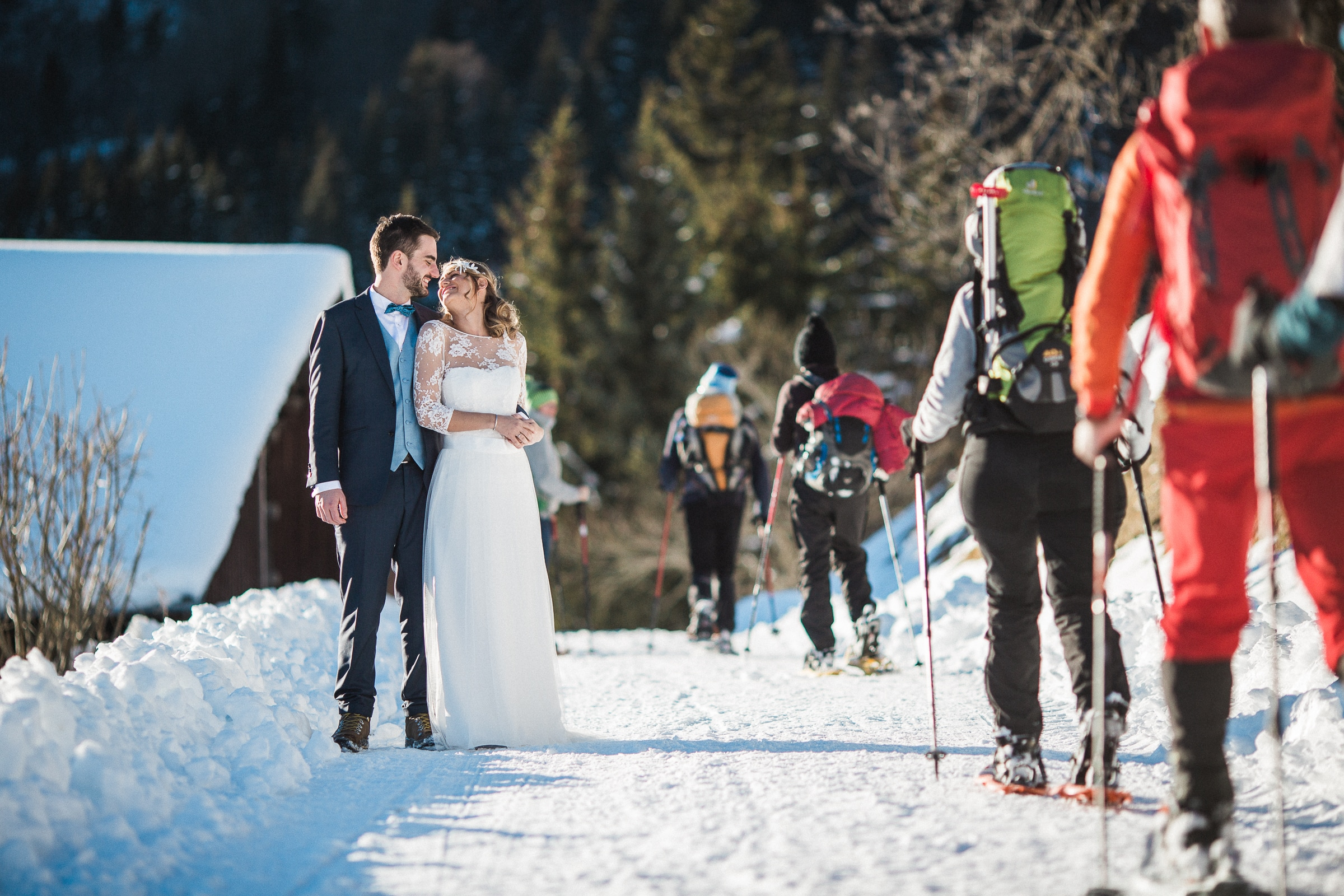 couple-portrait-in-the-snow-with-passing-snowshoers-sylvain-bouzat-wedding-photographer