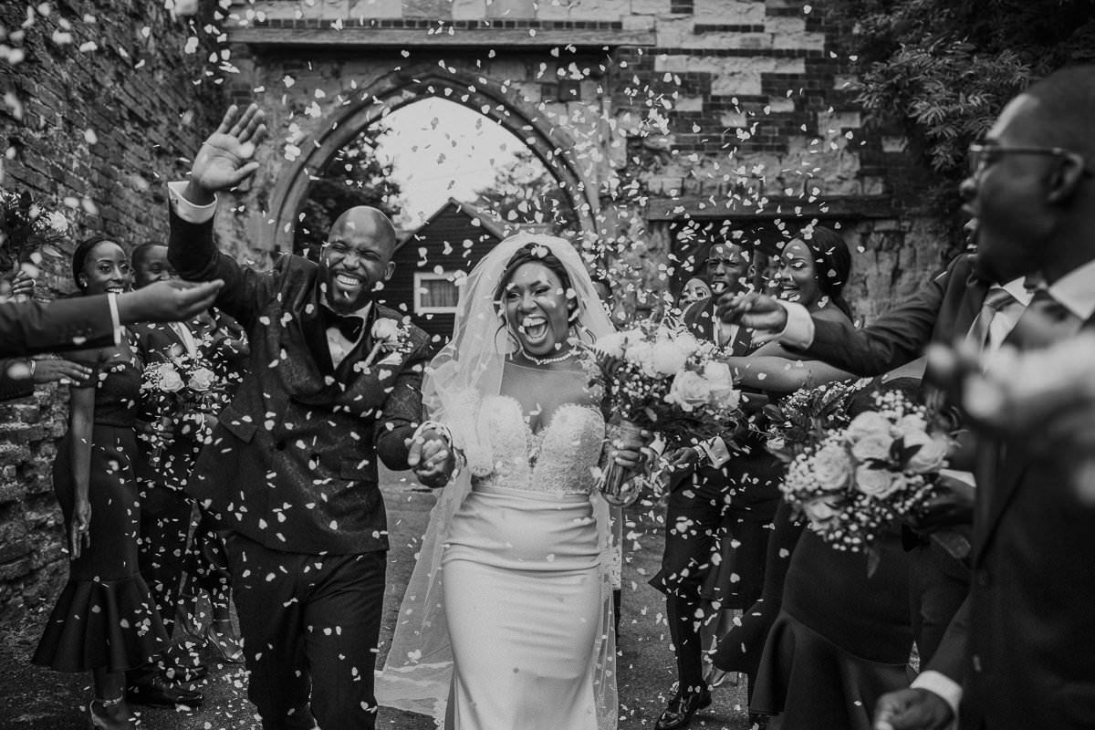 couple-showered-with-rose-petals-after-ceremony-photo-by-motiejus-england