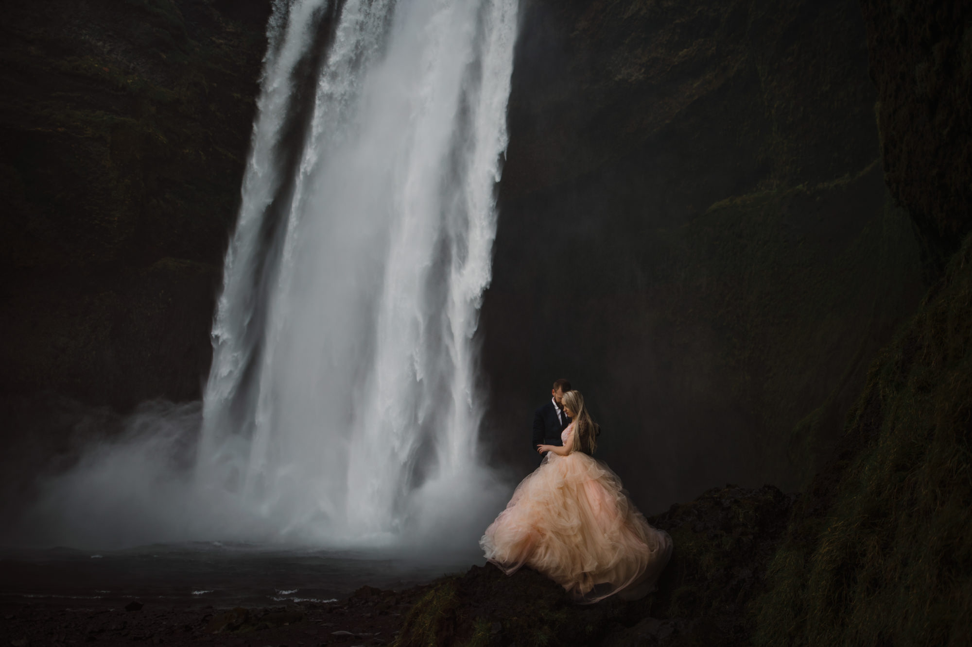 Bride at waterfall in pink tulle wedding dress - photo by Gabe McClintock - Alberta