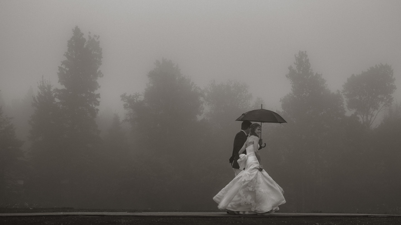 Couple walking through fog and rain photographed by Joel and Justyna - Ottawa wedding photographers