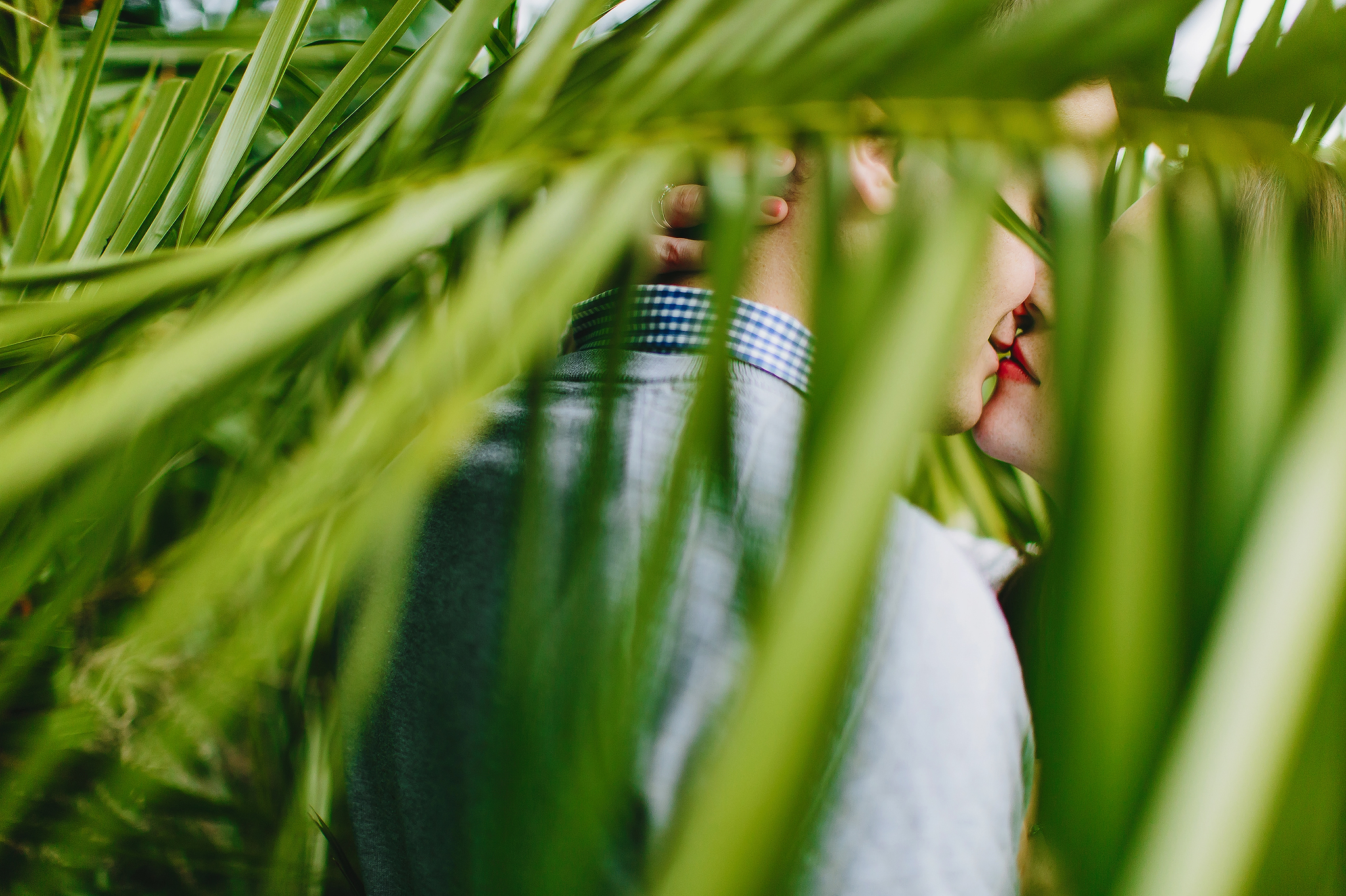 Bride with bright red lipstick kisses her groom behind green palm fronds - photo by Ruan Redelinghuys