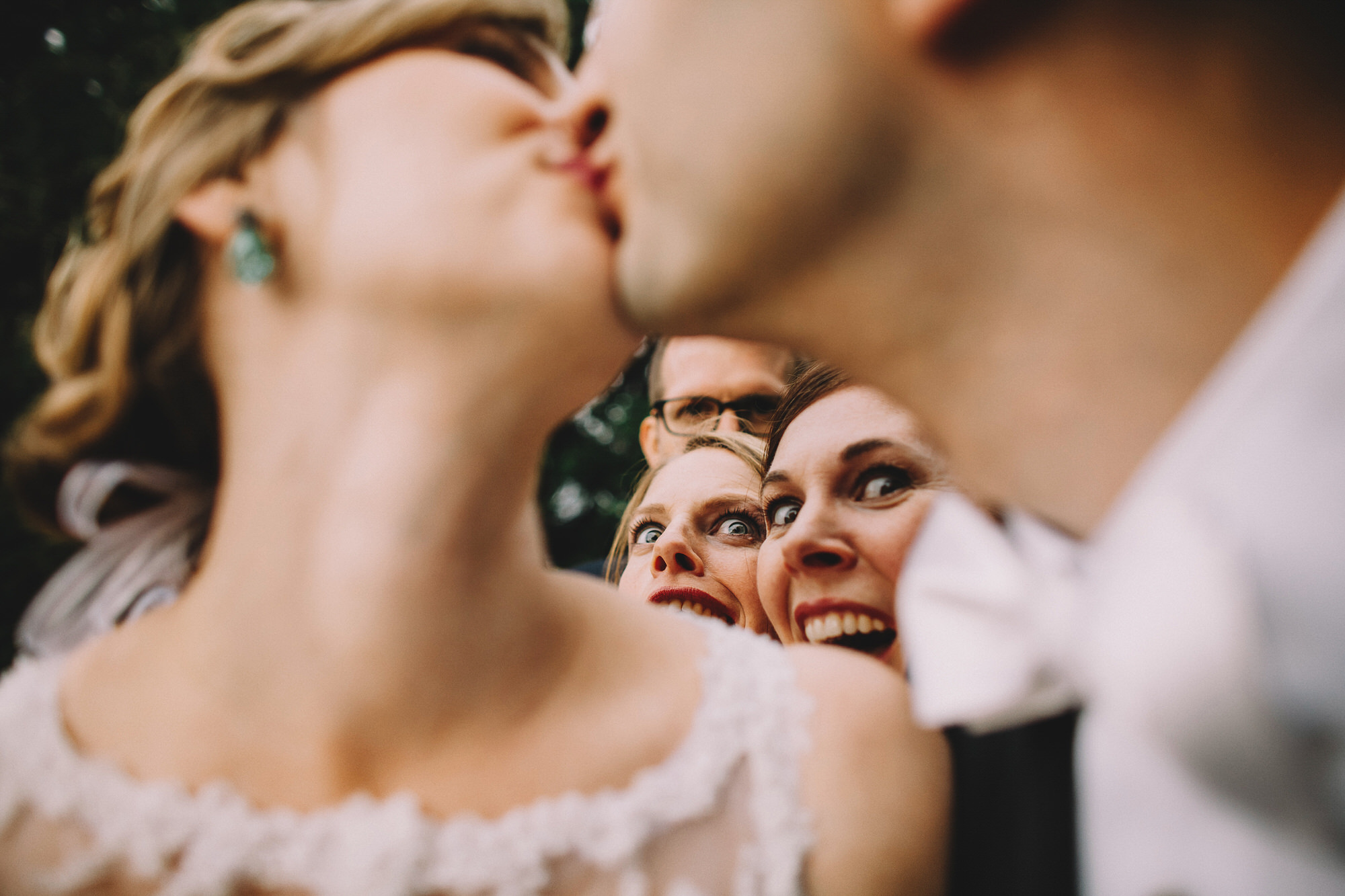 creative-composition-of-bride-and-groom-kissing-with-friends-watching-by-ken-pak-washington-dc-photographer