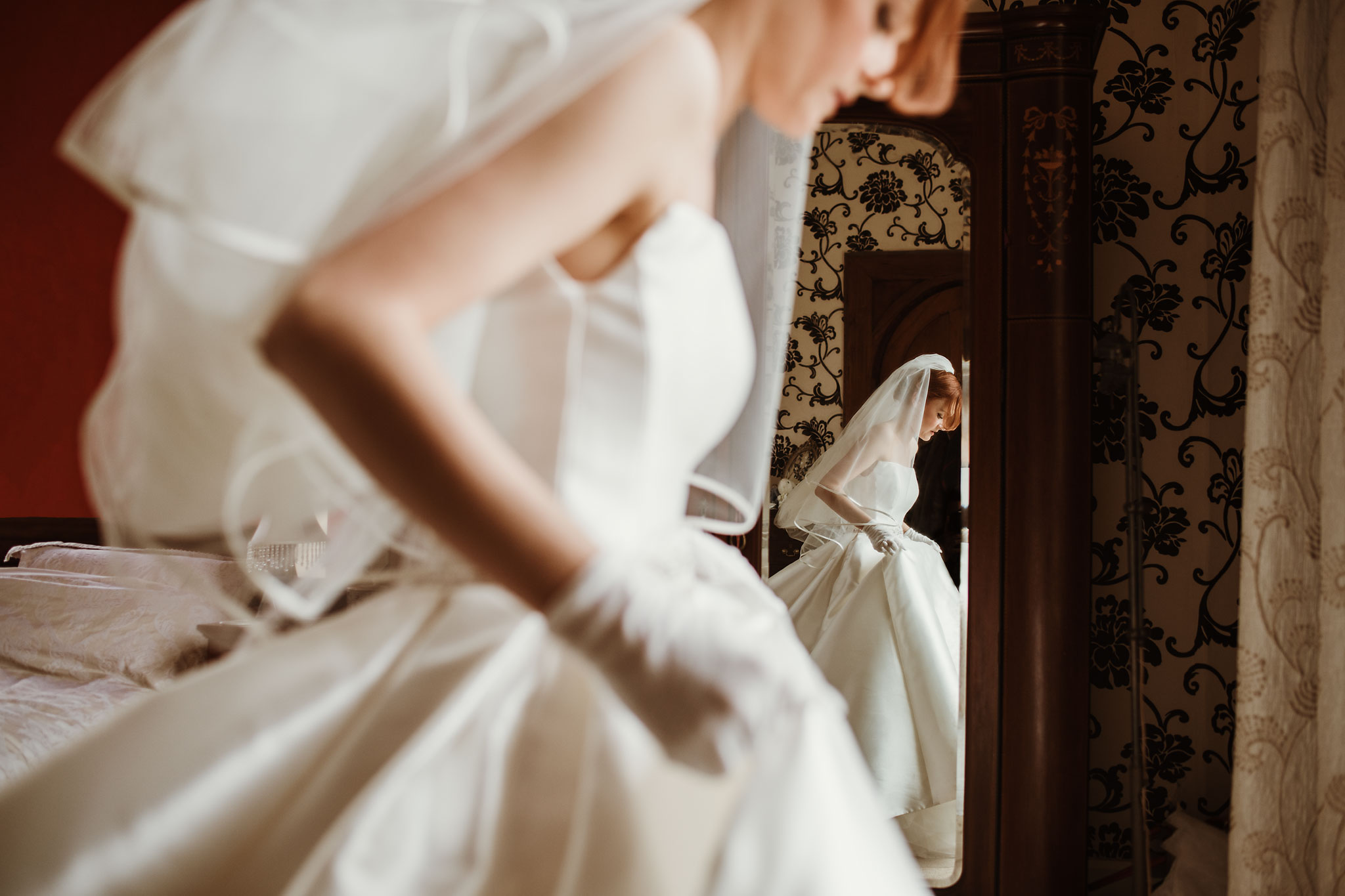 Bride reflected in mirror as she leaves for the ceremony - photo by Rich Howman - England