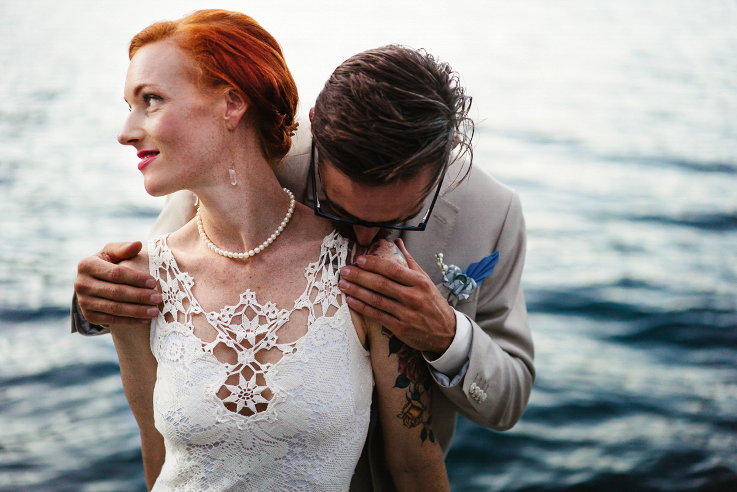 Bride wearing lace applique dress on beach with groom - photo by Sasha Reiko