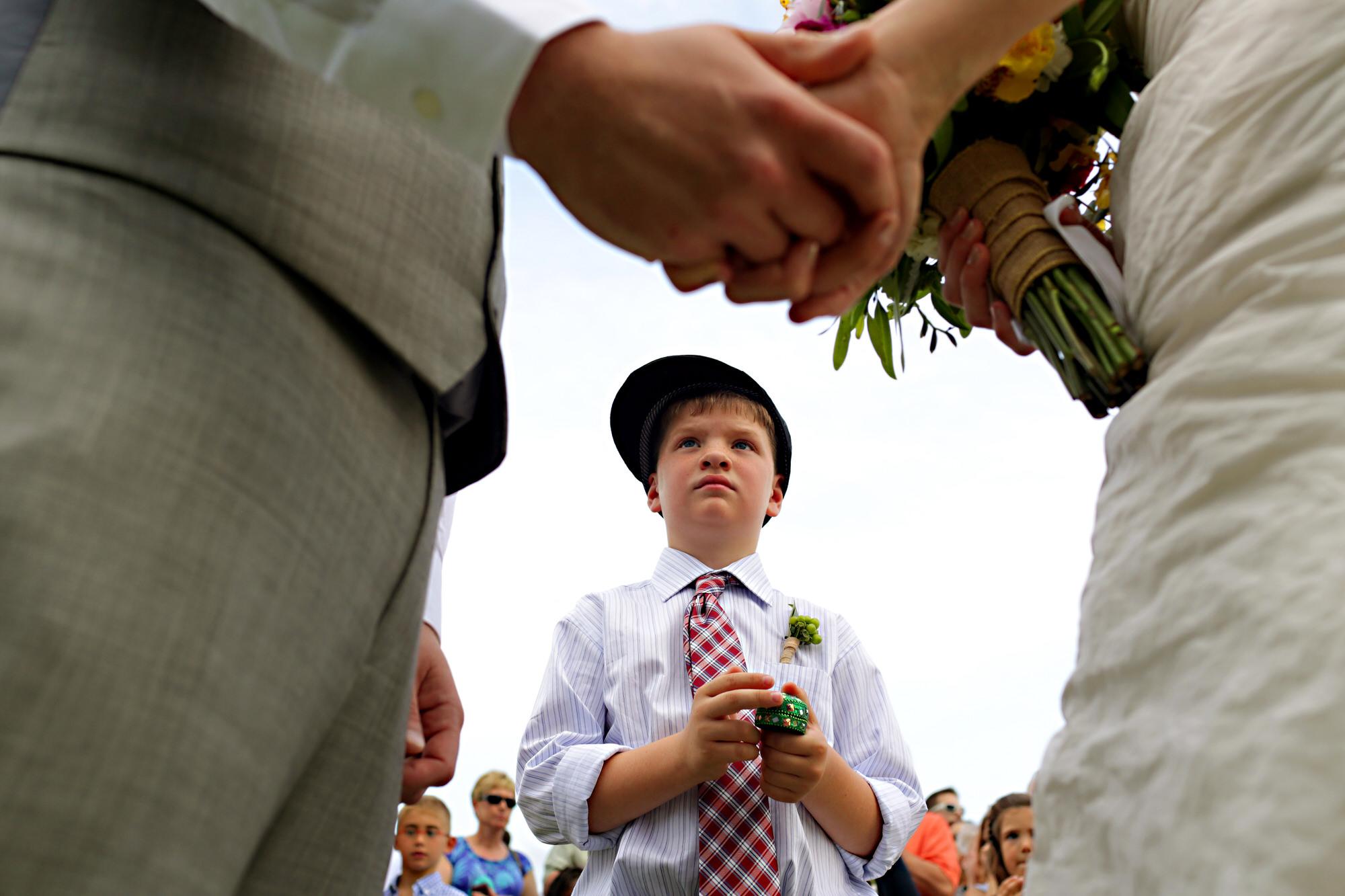 cute-ringbearer-during-wedding-ceremony-framed-by-bride-and-groom-worlds-best-wedding-photos-tyler-wirken-kansas-city-wedding-photographers