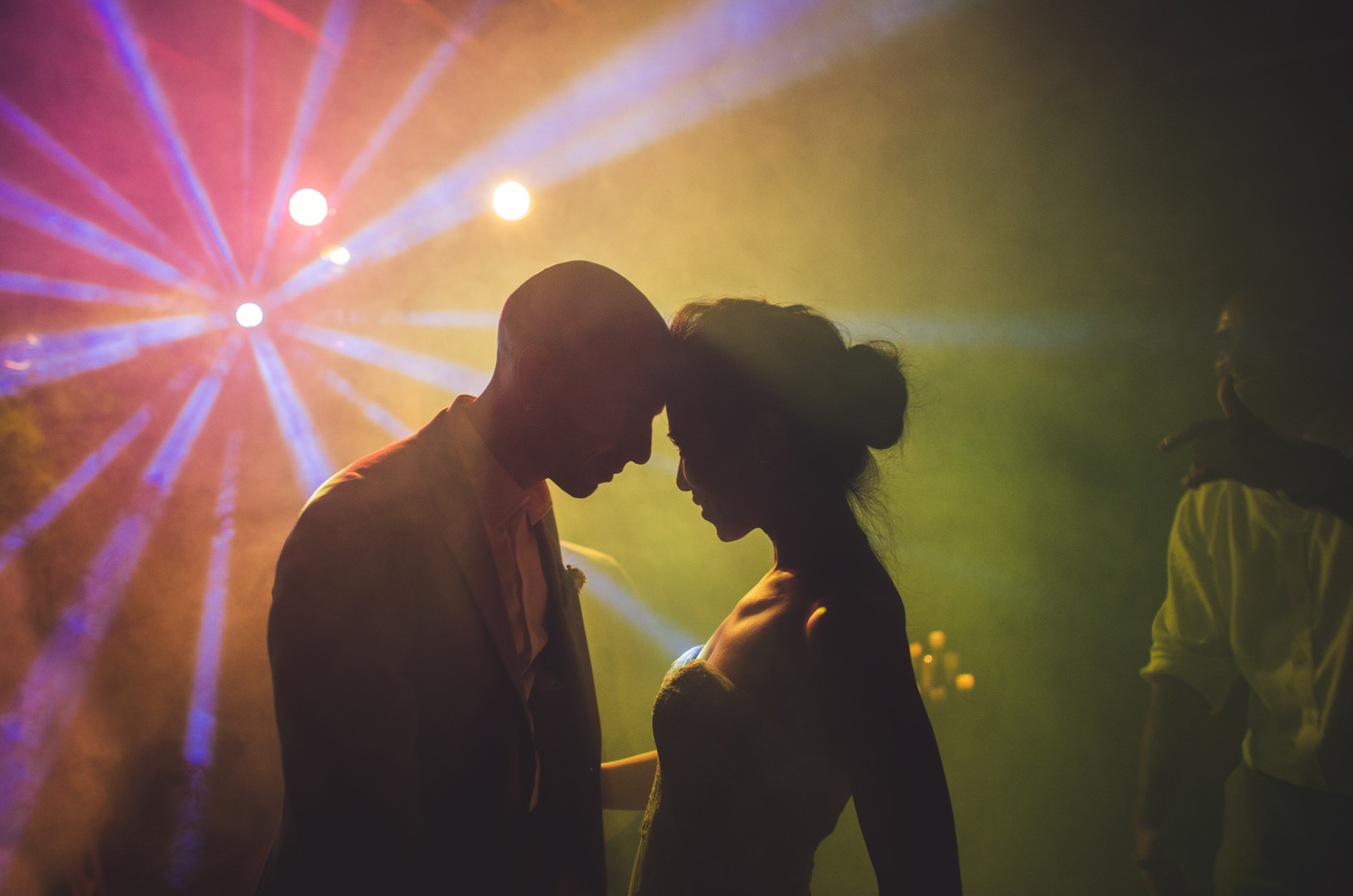 Couple in colorful dance floor light show during reception by Jeff Newsom, San Luis Obispo