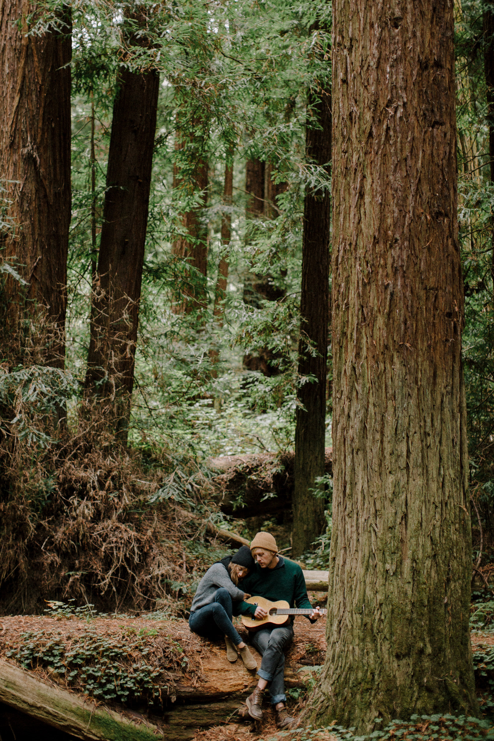 Couple playing guitar in forest by Nirav Patel of San Francisco