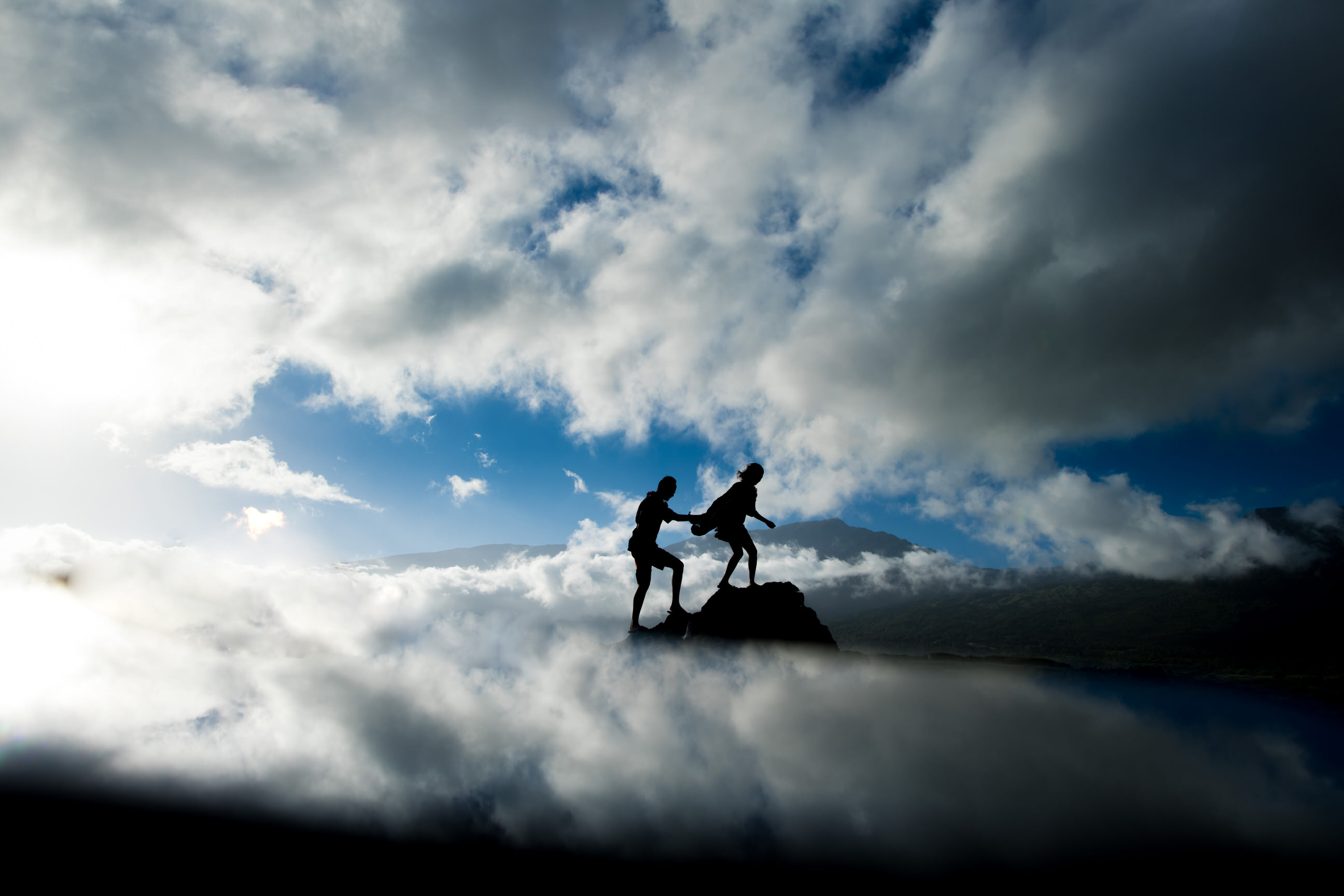 engagement-couple-on-mountain-summit-against-clouds-angela-nelson-photography.
