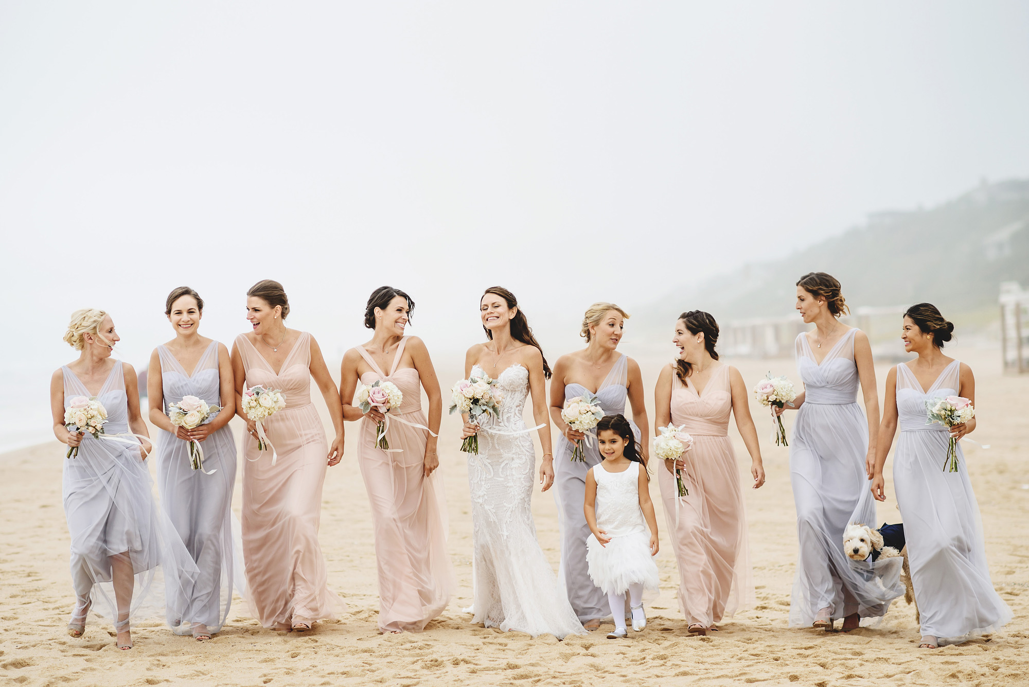 Bridesmaids wearing lavender and blush chiffon wedding gowns on beach with bride - photo by Ross Harvey - London
