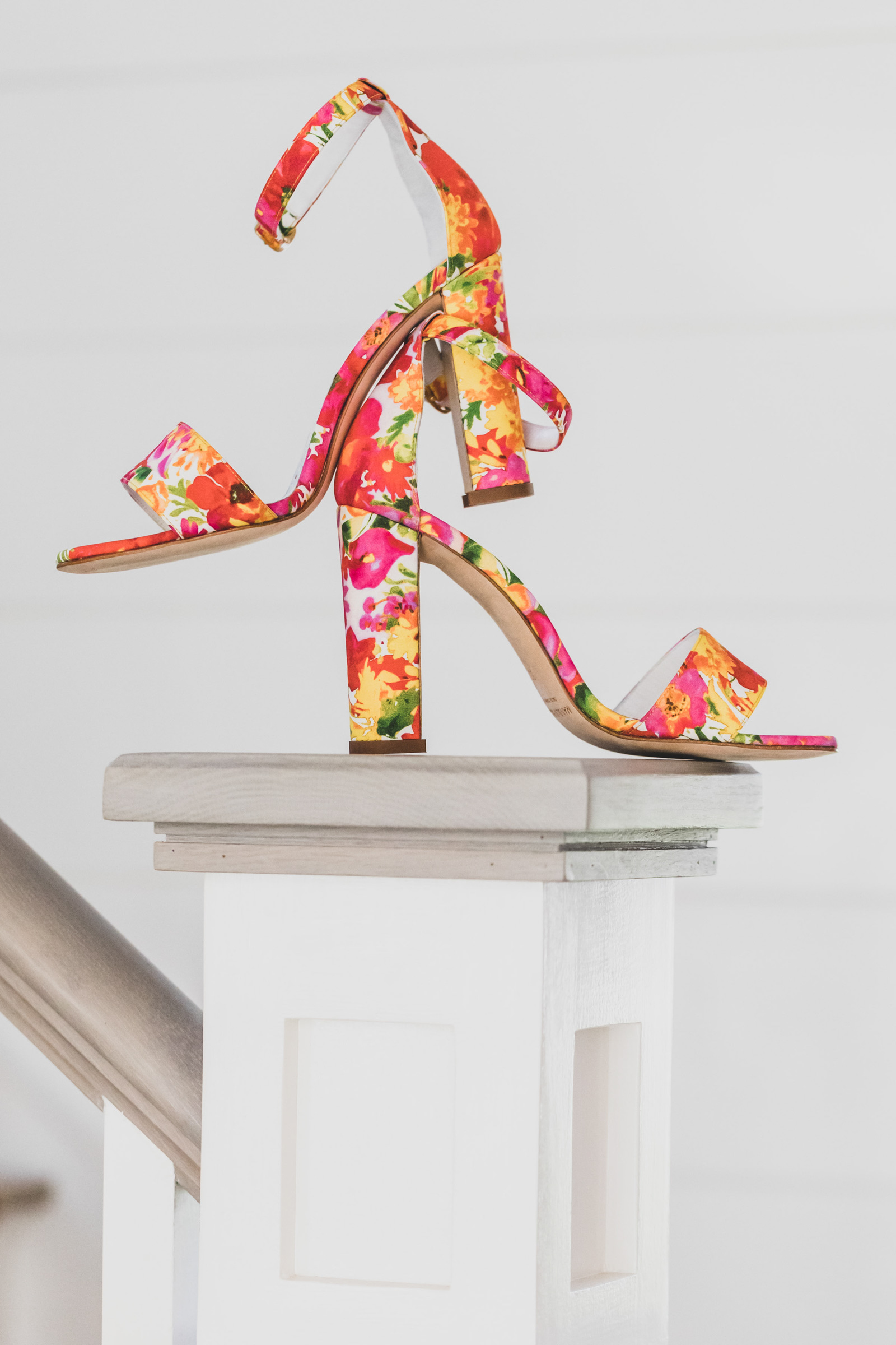Sandals with red, pink, and yellow floral pattern photographed by Katie Kaiser