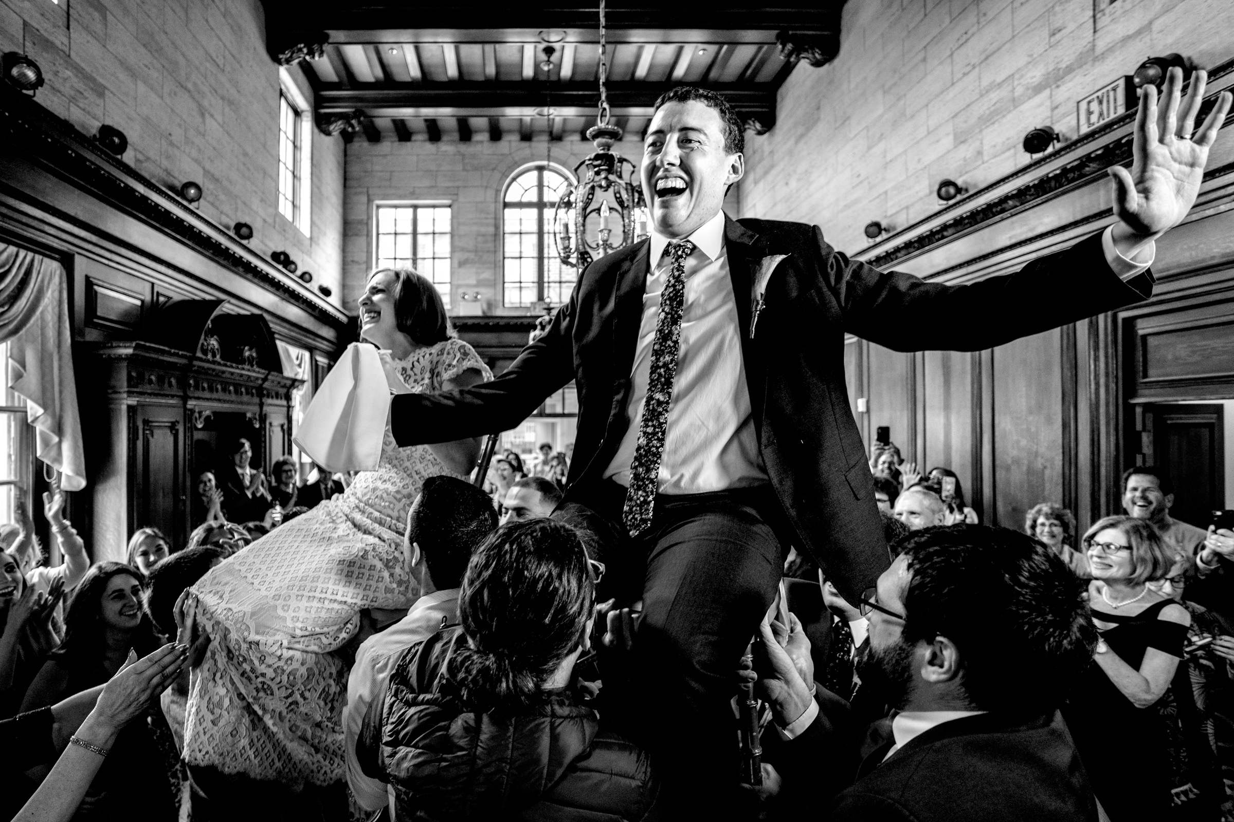 Bride and groom above the crowd during Hora dance - photo by Bee Two Sweet