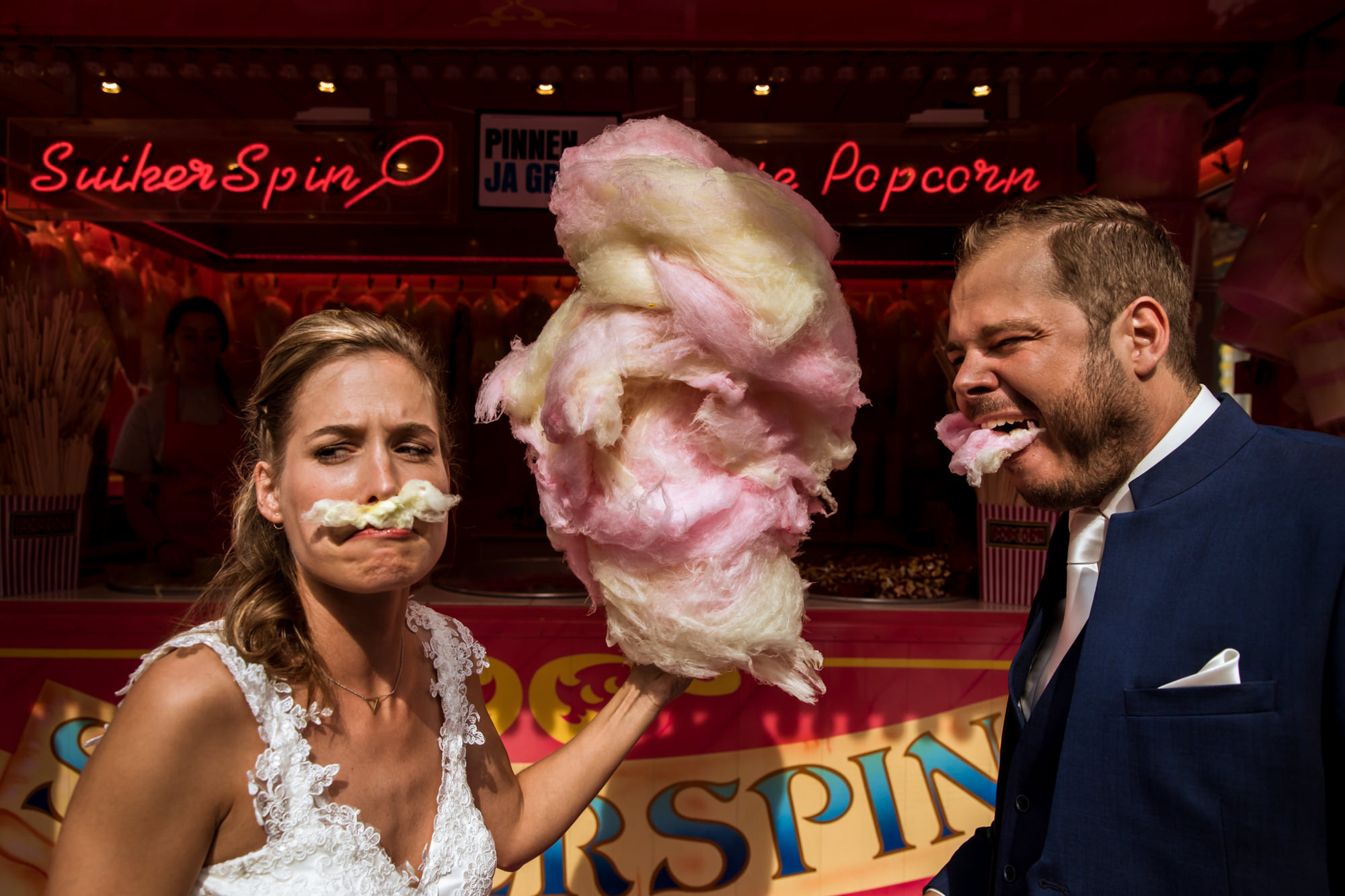 funny-bride-and-groom-portrait-eating-cotton-candy-worlds-best-wedding-photos-fotobelle-netherlands-wedding-photographers
