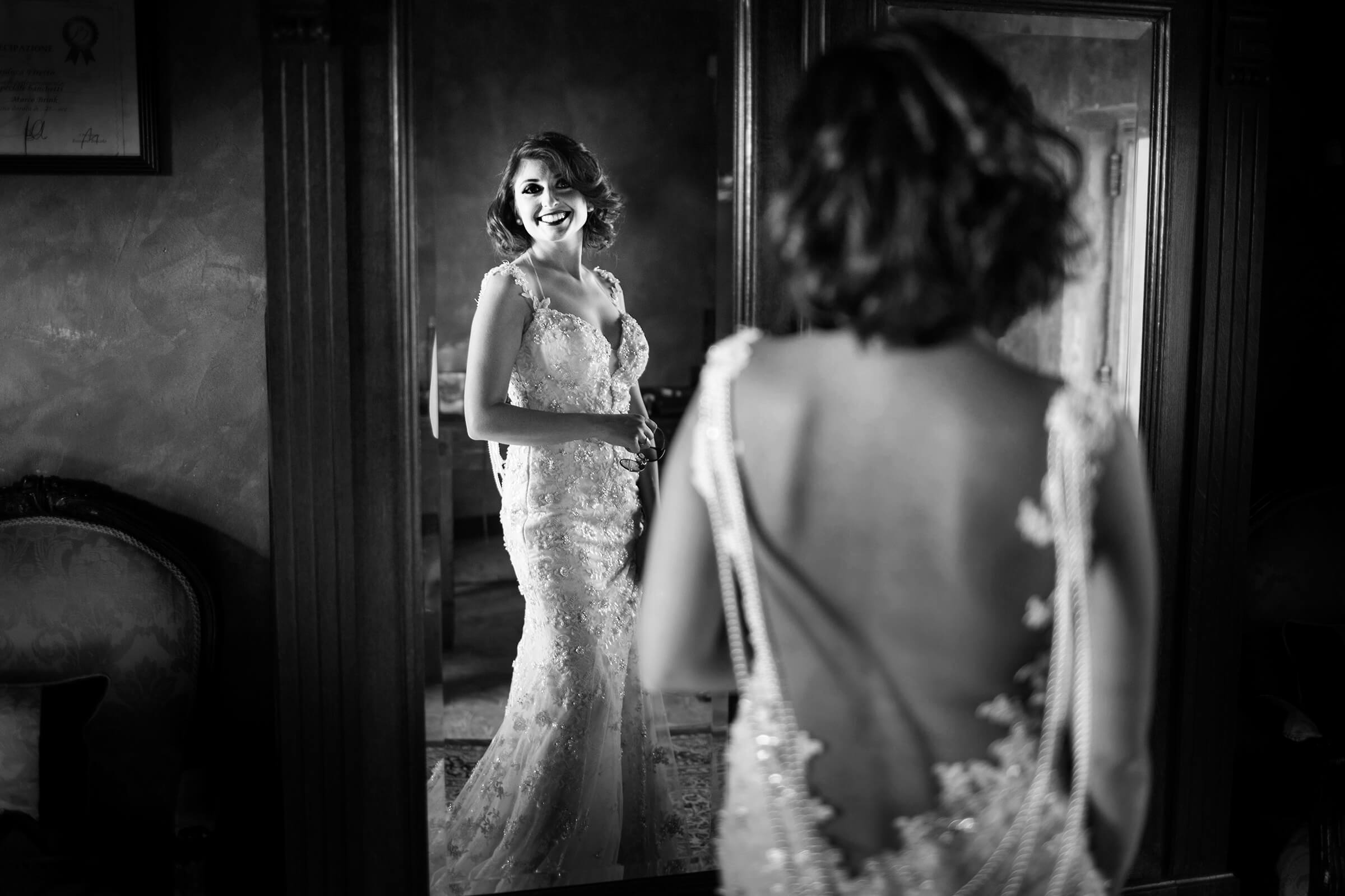 Glamourous bride smiles at her reflection - photo by Nino Lombardo - Italy
