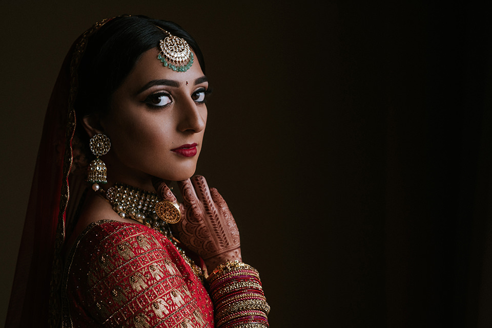 Bride wearing Indian attire with dramatic black eyeliner and ruby red lips - photo by Charmi Pena - New York