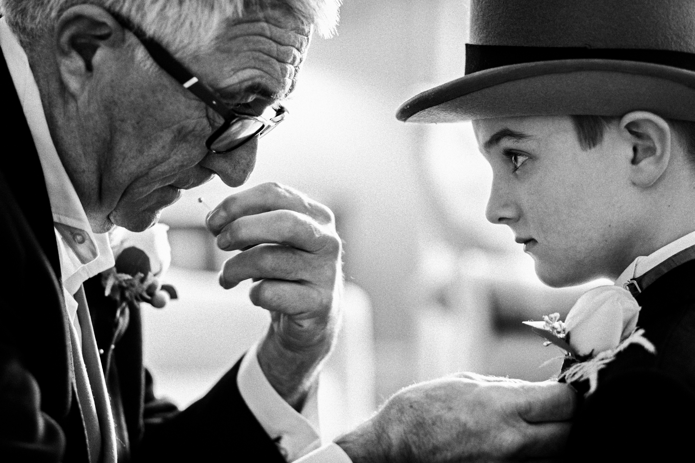 Grandfather pins on boutonniere of grandson wearing top hat - photo by Jeff Ascough