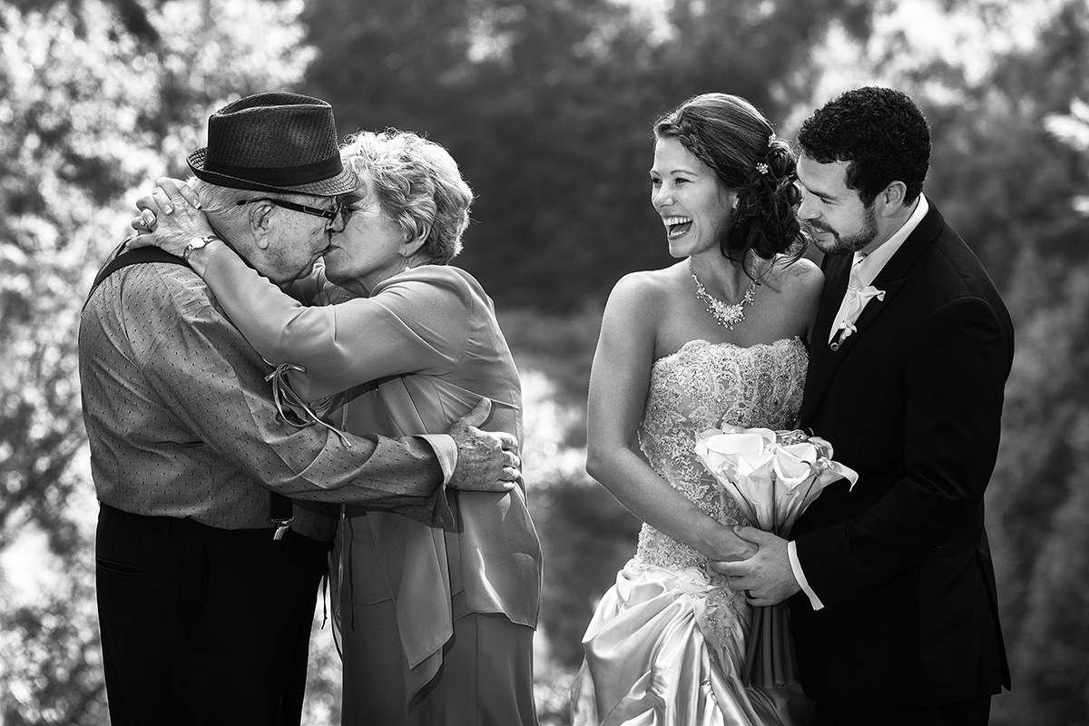 Grandparents kiss while bride and groom look on - photo by Amber Henry - Michigan