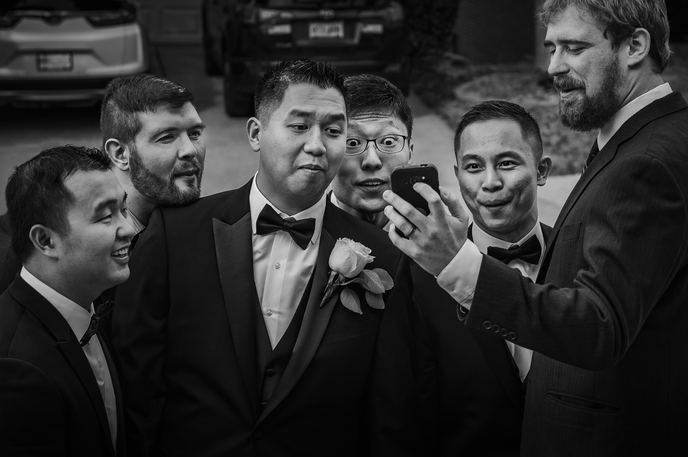 groom-and-groomsmen-peering-at-phone-viridian-images-photography
