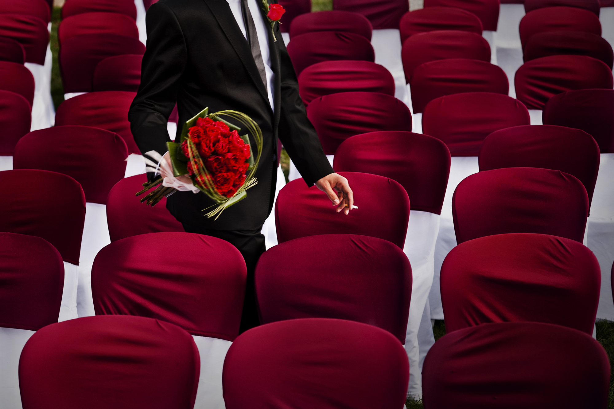 groom-holding-bouquet-of-red-roses-among-rows-of-chairs-worlds-best-wedding-photos-victor-lax-spain-wedding-photographers