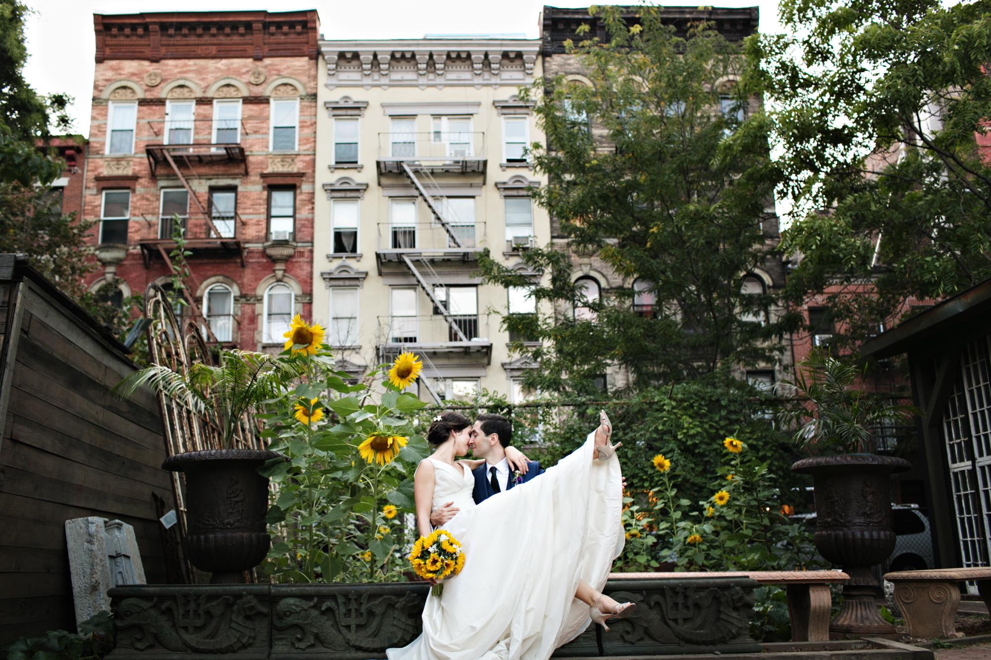 Seattle groom lifts bride off her feet in sunflower garden - photo by Photo JJ