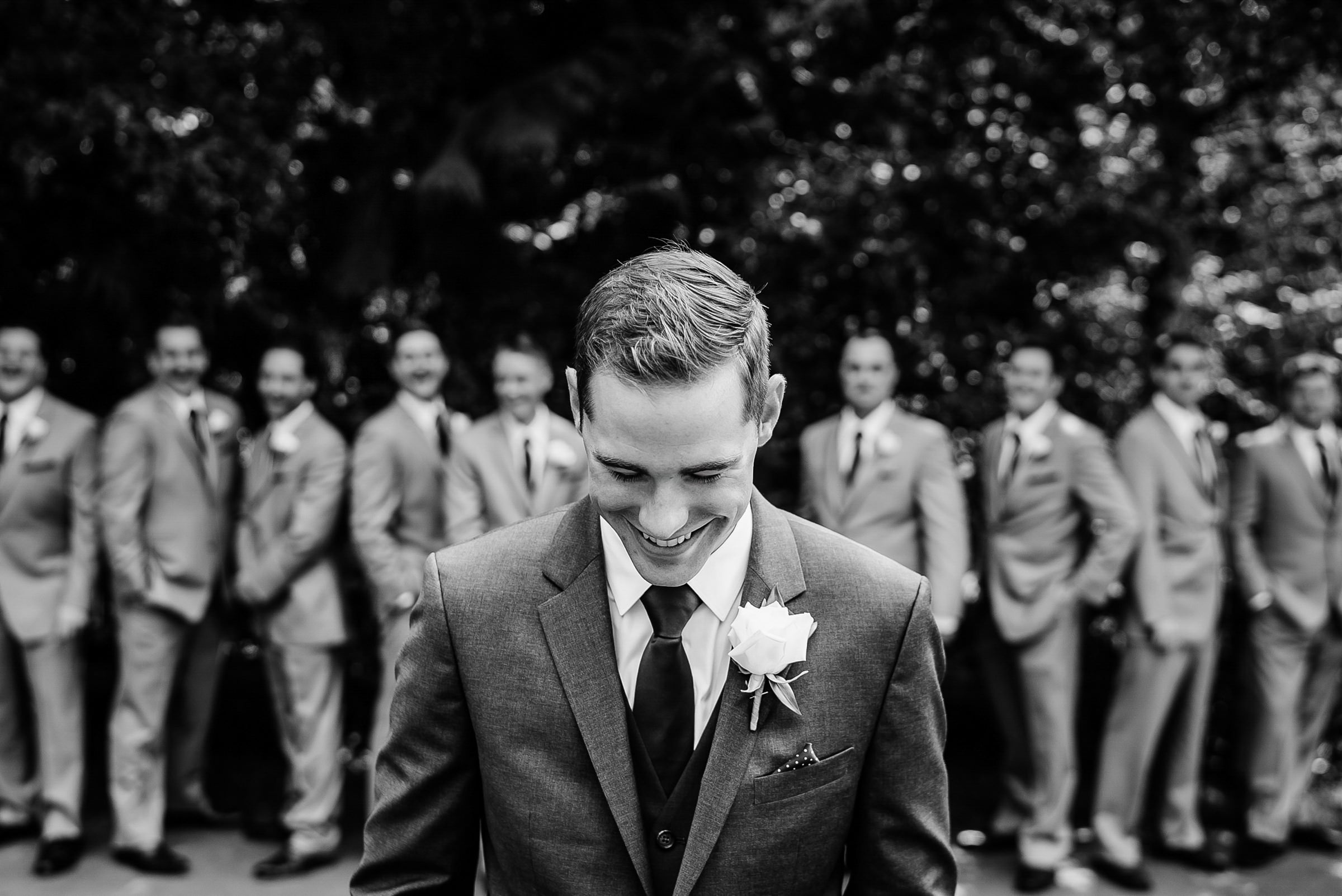 groom-portrait-against-line-of-groomsmen-sasha-reiko-photography
