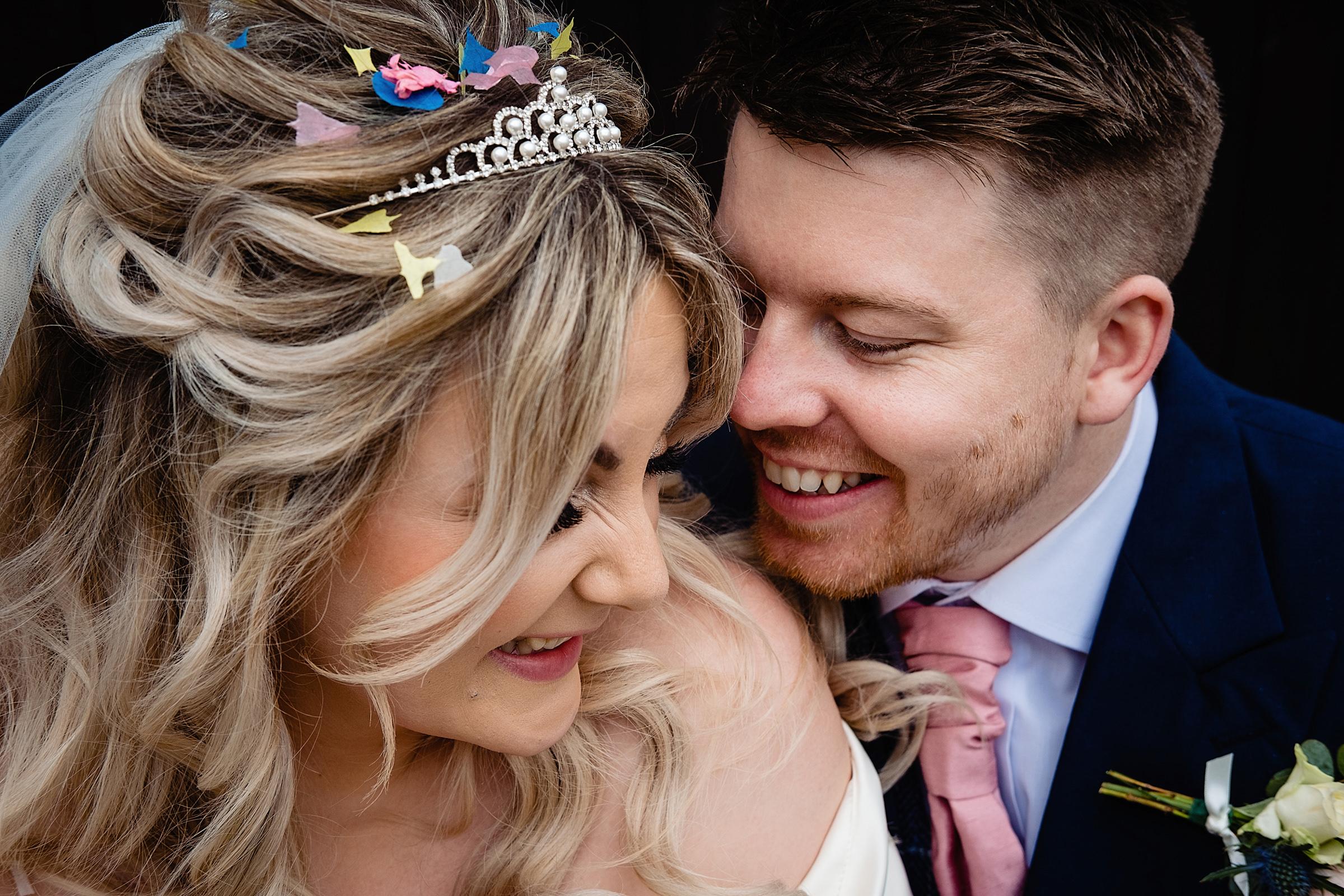 groom-snuggles-bride-wearing-tiara-with-confetti-emmaplusrich-england