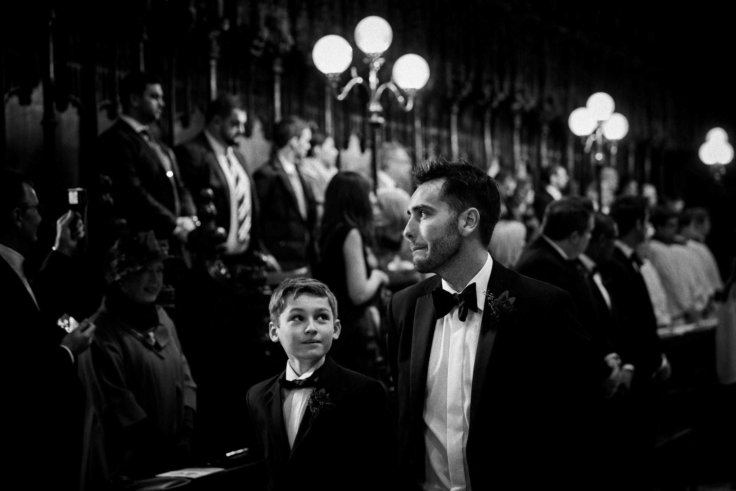 Boy looks up at his crying father during ceremony - documentary wedding photo by Jeff Ascough