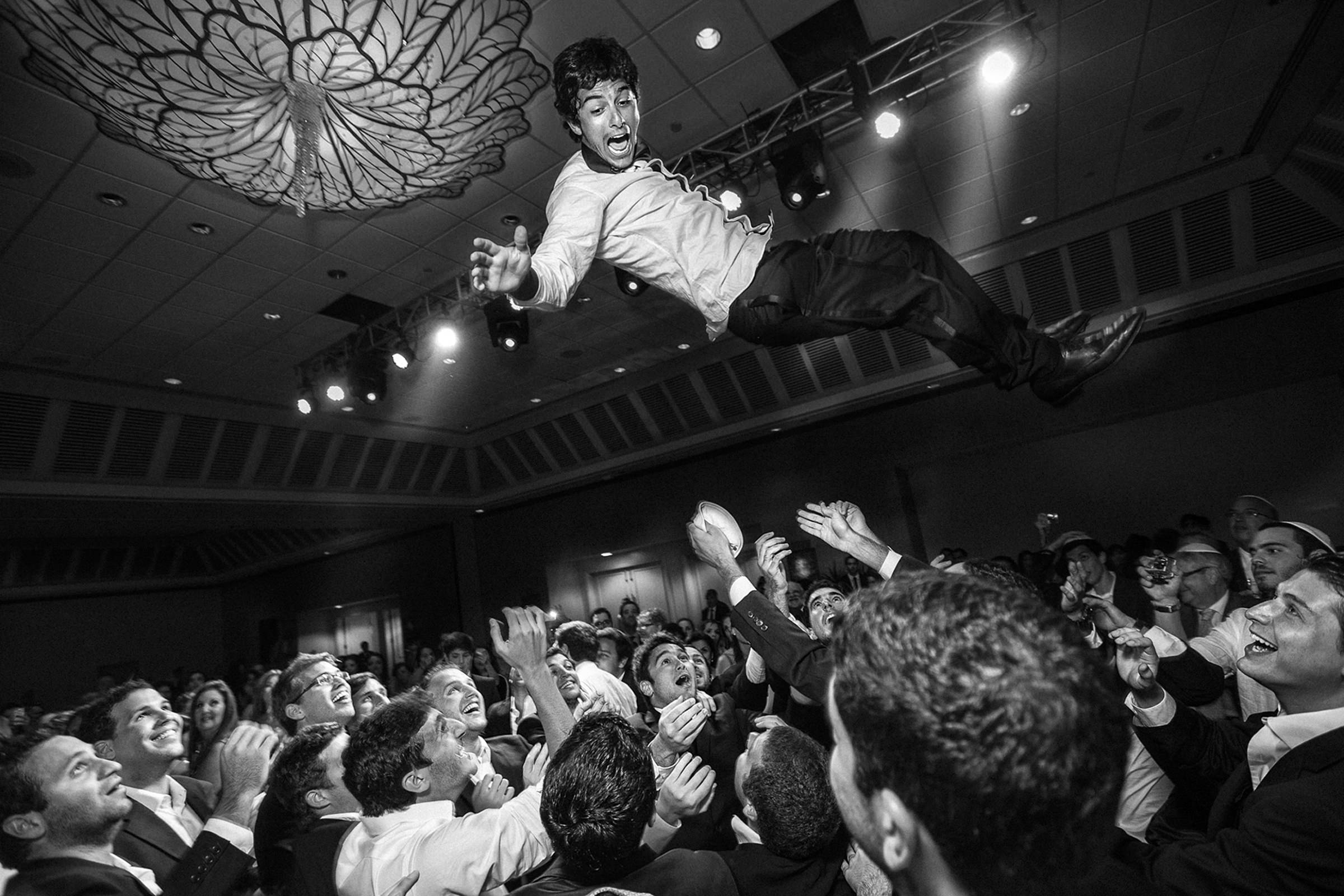 Groom tossed above crowd at wedding reception - photo by El Marco Rojo