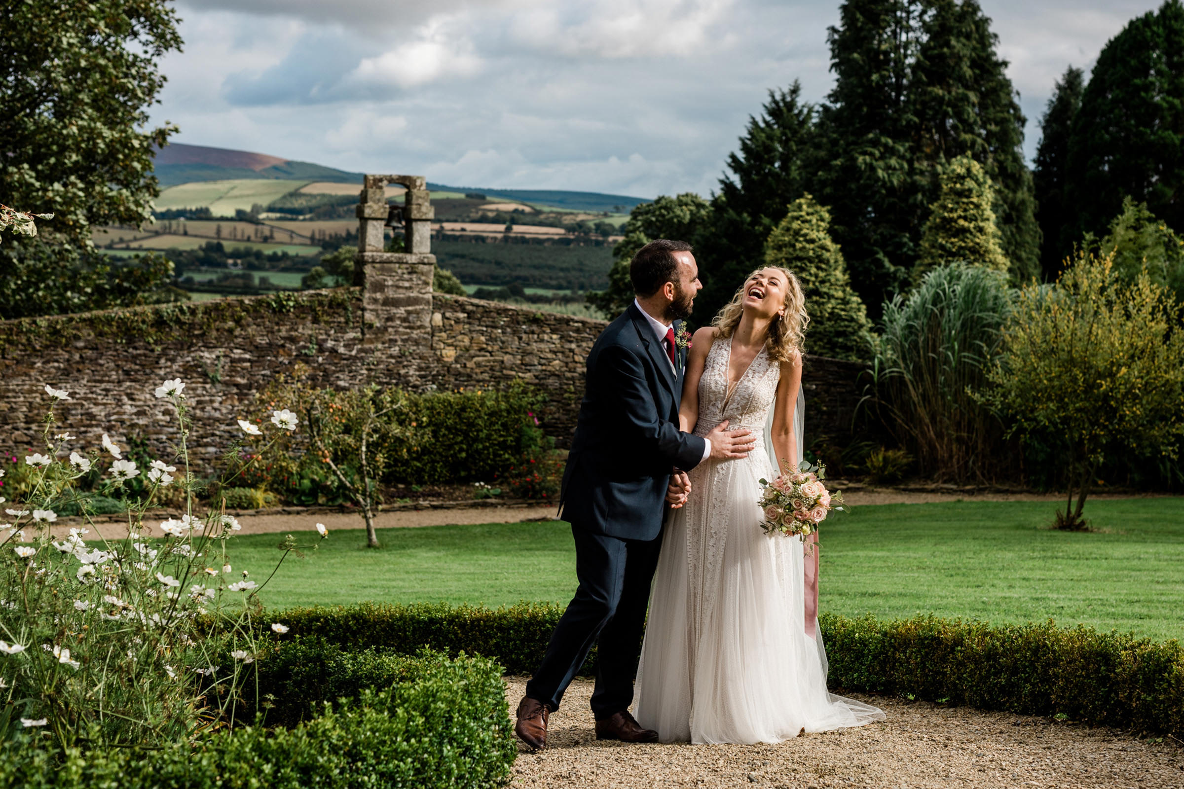 groom-with-laughing-bride-against-stone-wall-and-countryside-the-portrait-rooms