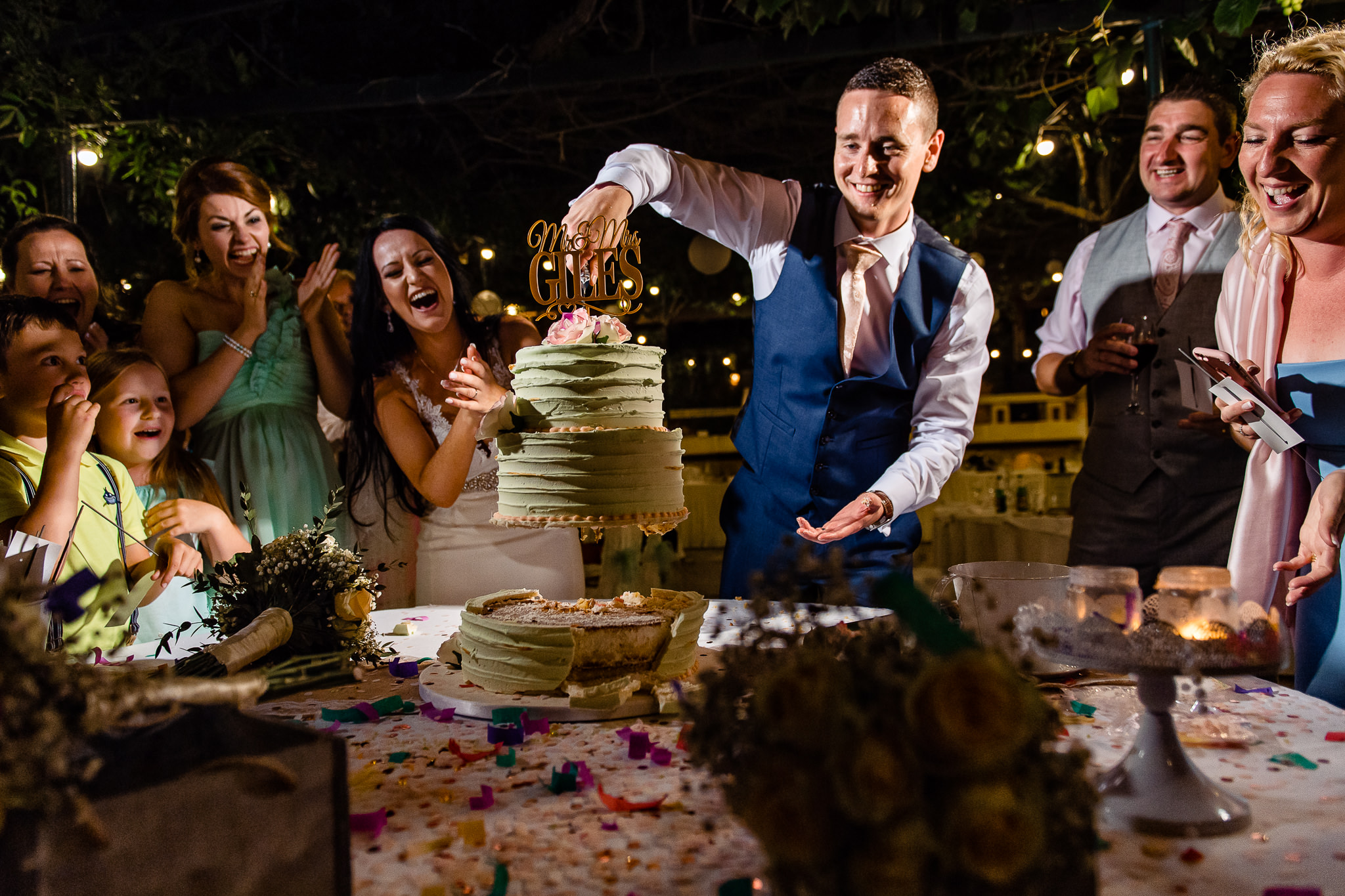 Groom pulls wedding cake apart with cake topper - photo by Shane P. Watts - Malta