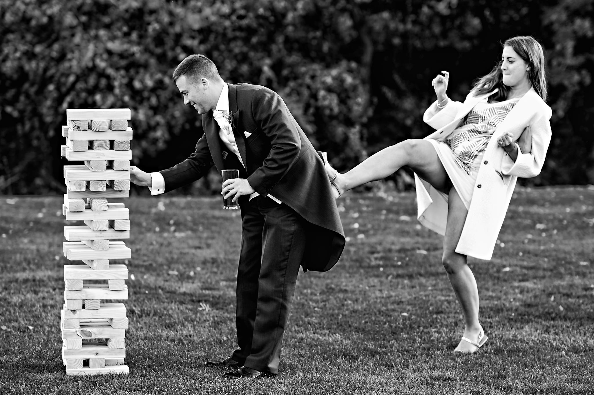 Guest pushes groom while he's playing Jenga - photo by Rich Howman